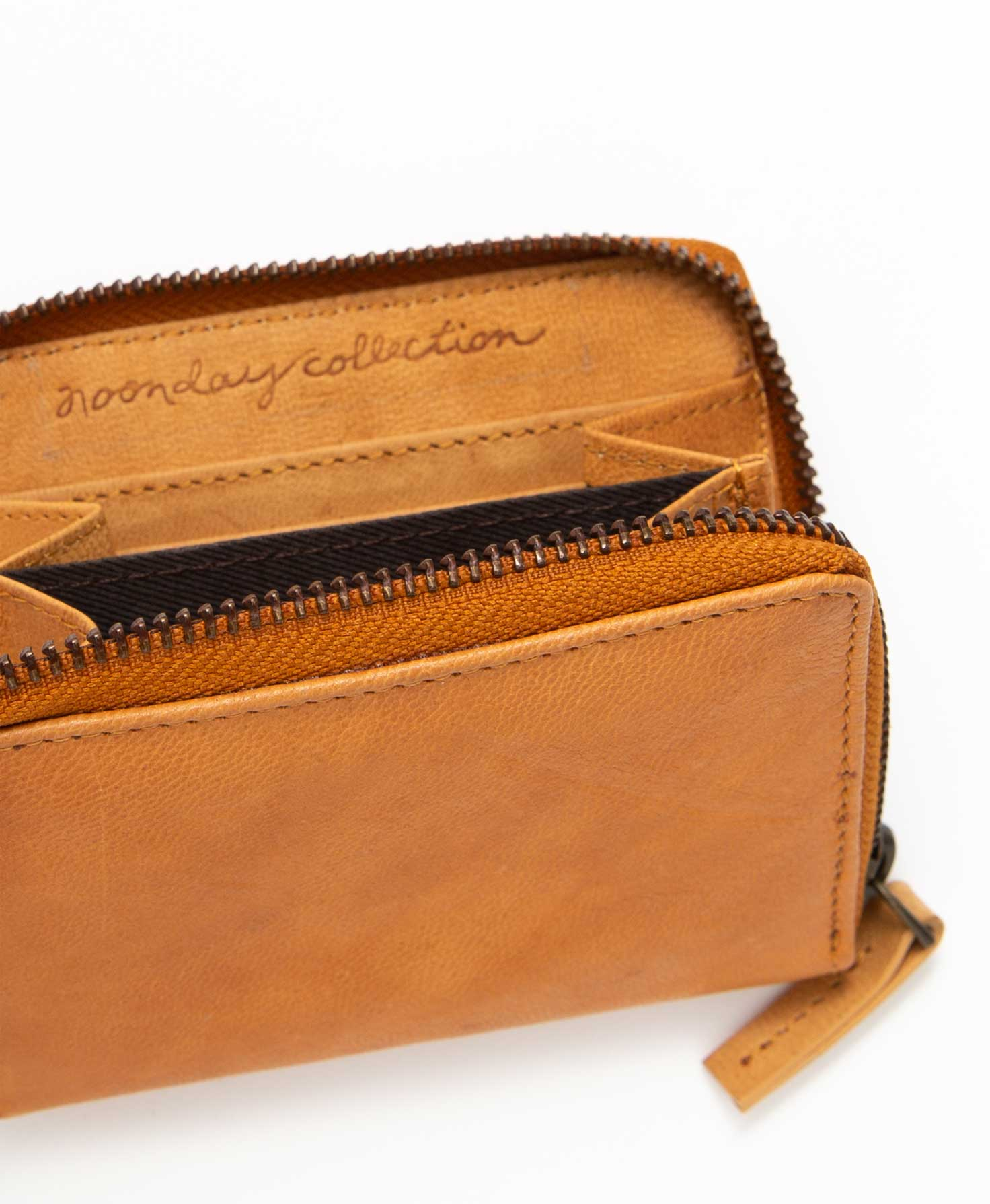The Essential Leather Wallet sits upright. It is unzipped, revealing the inside of the wallet. The interior is the same neutral leather as the exterior. There is a Noonday Collection logo embossed on the inside. A few of the wallet's six internal card slots can be seen.