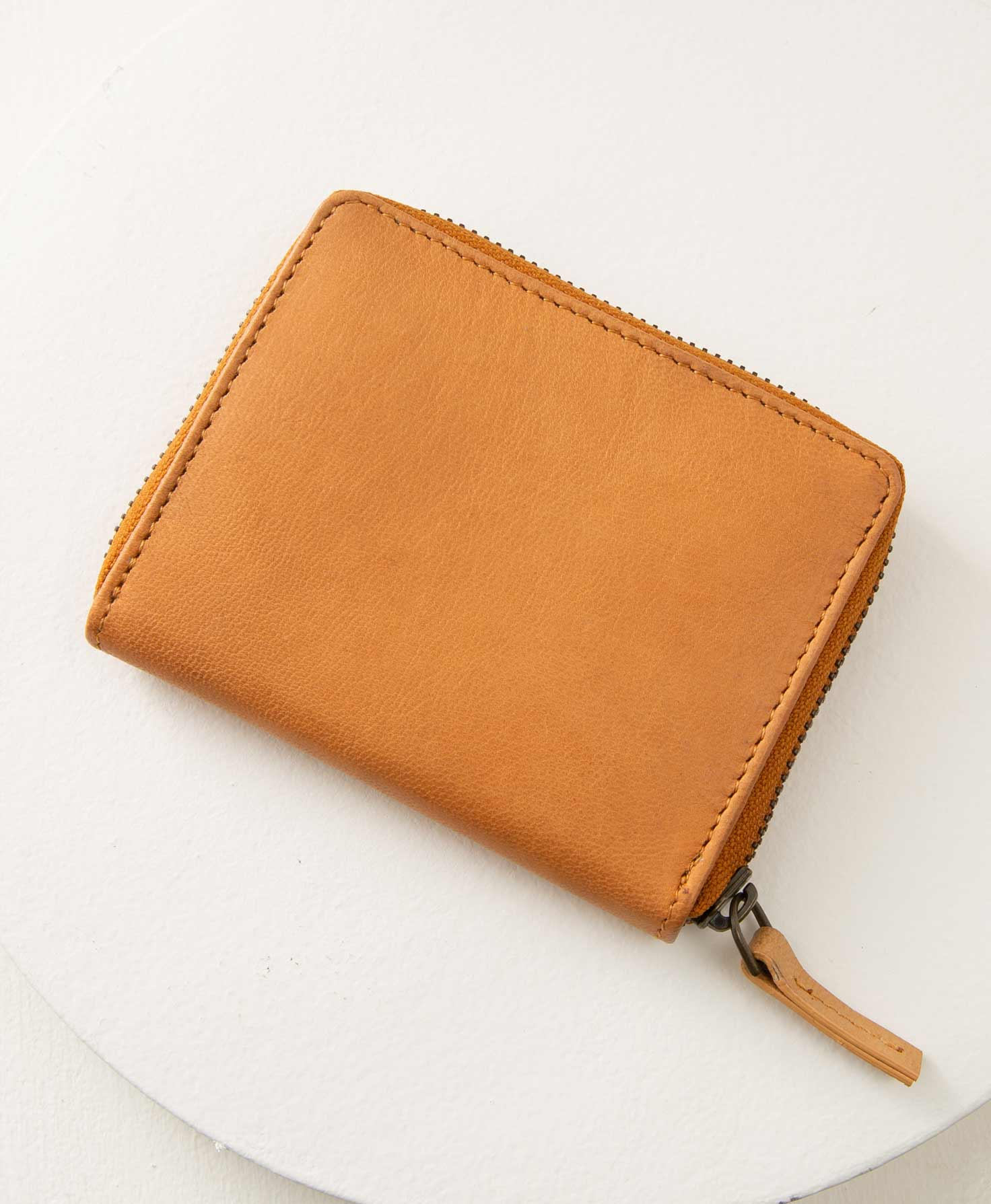 The Essential Leather Wallet rests on its side on a white surface. It is a simple, roughly square-shaped wallet that is slightly wider than it is tall. It is composed entirely of matte, caramel-colored leather. A bronze zipper wraps around the sides and top of the wallet and is finished with a leather zip pull.
