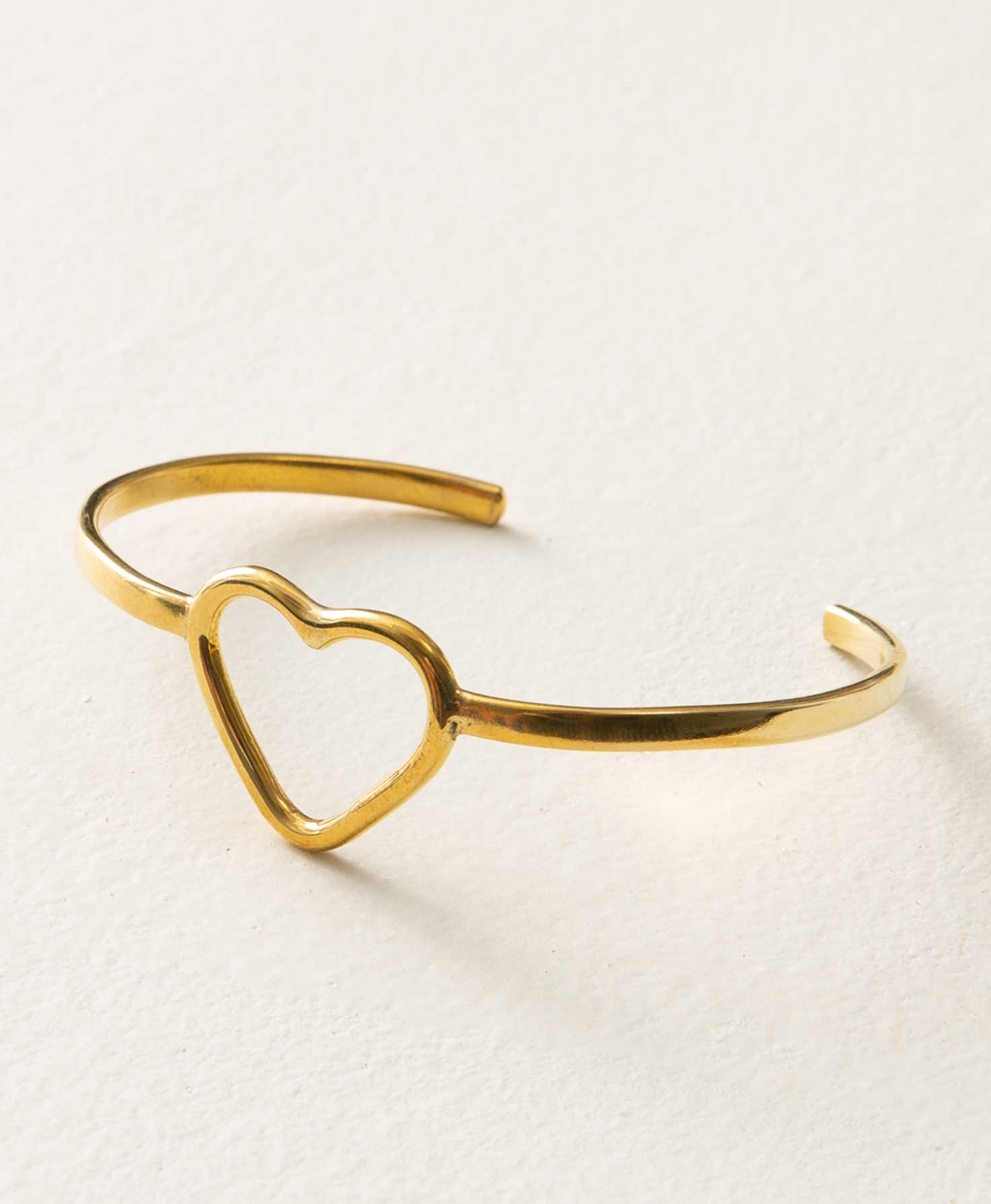 The Expression Cuff sits on a white background. A thin, flat bar of brass curves around and meets a brass heart in the center of the bracelet. The heart is roughly one inch tall and wide. It is composed of a brass outline that forms its shape, and is open in the middle. There is an opening in the back of the cuff where it can be slid onto the wrist.
