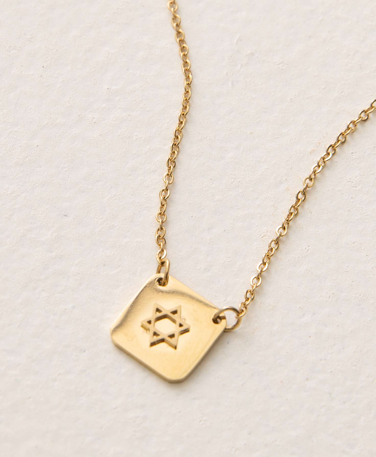 The Faithful Necklace rests on a white background. It features a gold chain with a small square pendant at the bottom. The pendant is connected to either side of the chain via metal jump rings. It has a shiny finish and features a raised Star of David emblem at its center.