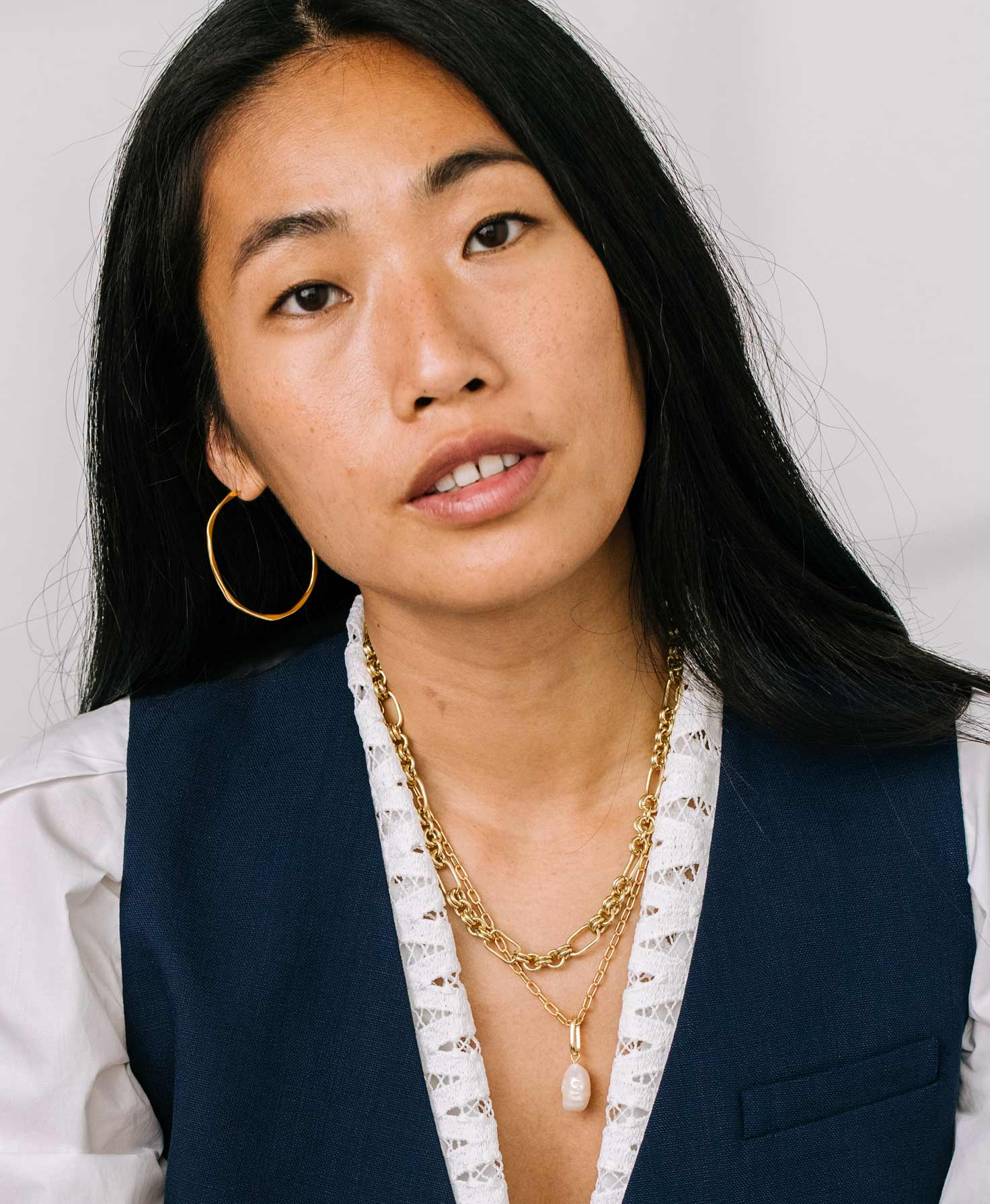 A model wears the Float Necklace layered with the Gold Rush Necklace, which has a similar gold chain with elongated links. She finishes her look with the Signal Hoops, which have the same shiny gold finish as the necklaces.