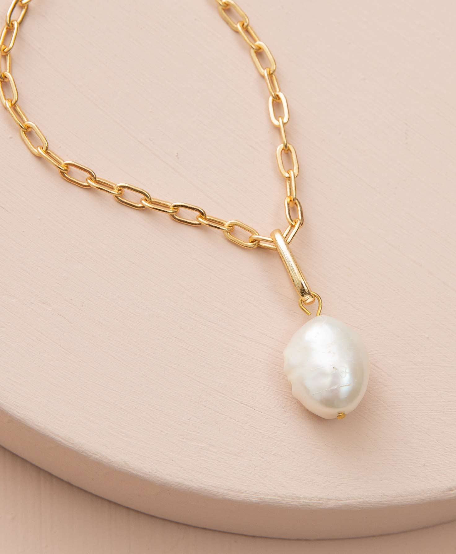 The Float Necklace rests on a cream-colored platform. It features a chain of shiny gold-plated brass links. The links are elongated and have a chain-link look. Attached to the chain is a small, vertical brass bar with a large round pearl dangling from it.