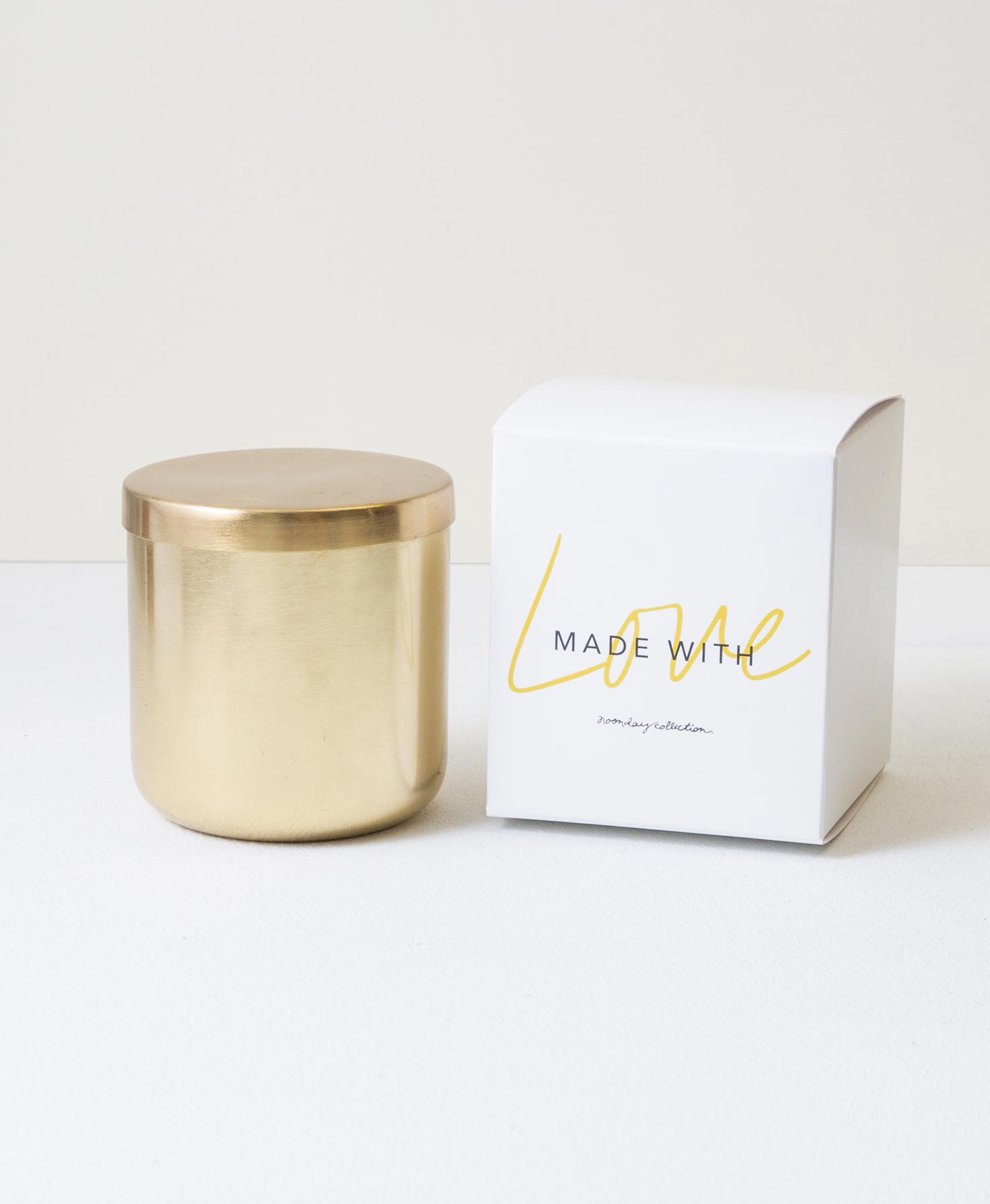 The Gather Candle sits with its brass lid on. The decorative box it is packaged in sits next to it. The box is white with