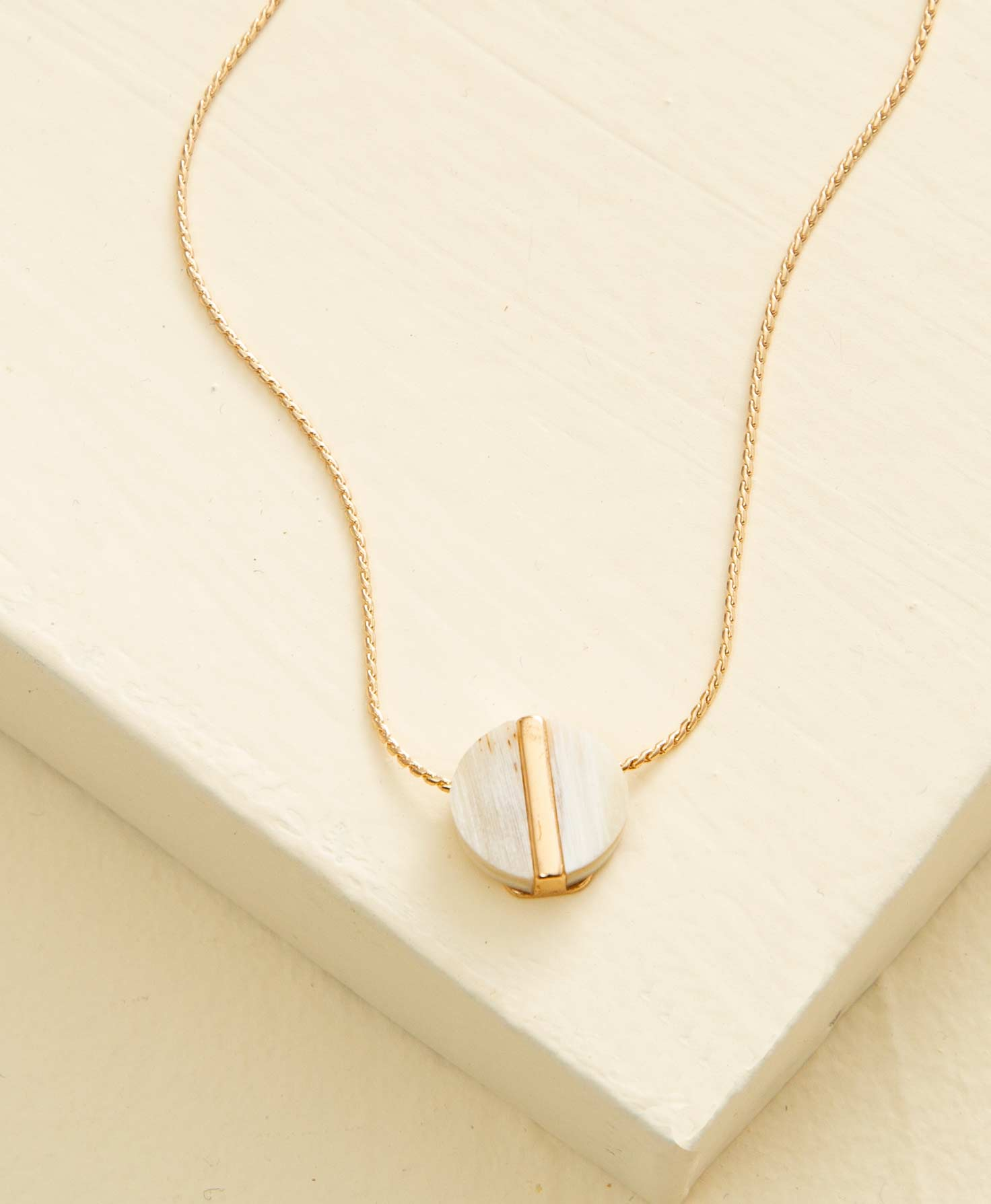 The Geo Necklace, Circle lays on a cream surface. It is a dainty necklace featuring a small, circular charm hanging from a gold chain. The charm is made of cream-colored horn with natural striations, and has a gold metal bar running vertically through its center.