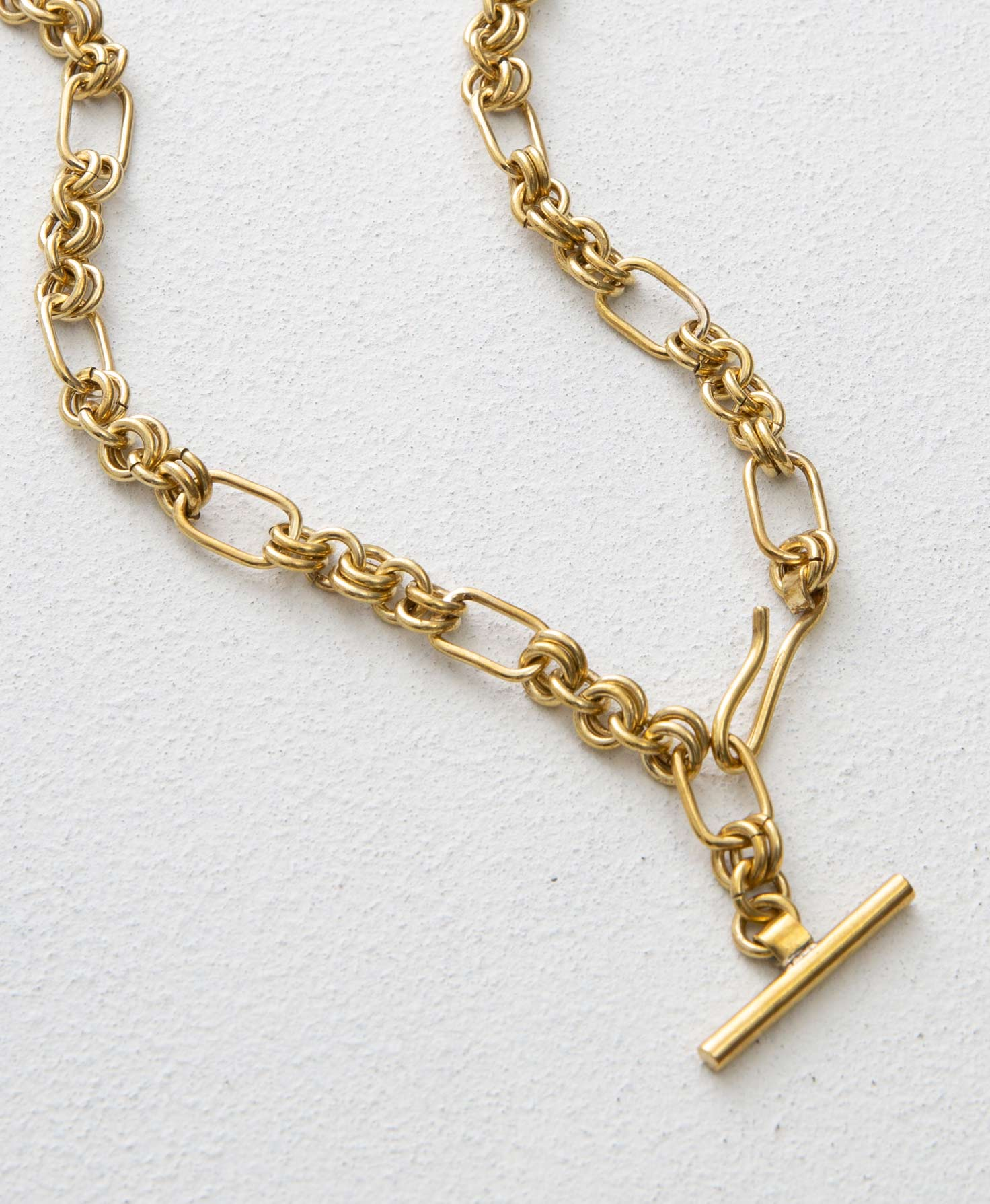 The Gold Rush Necklace lays on a white surface. It is made entirely of brass and features a chunky chain. The links of the chain alternate between circular links and bigger rectangular links. At one end of the chain is a brass hook that can be used to secure the necklace on any of the links. At the other end is a decorative brass bar.