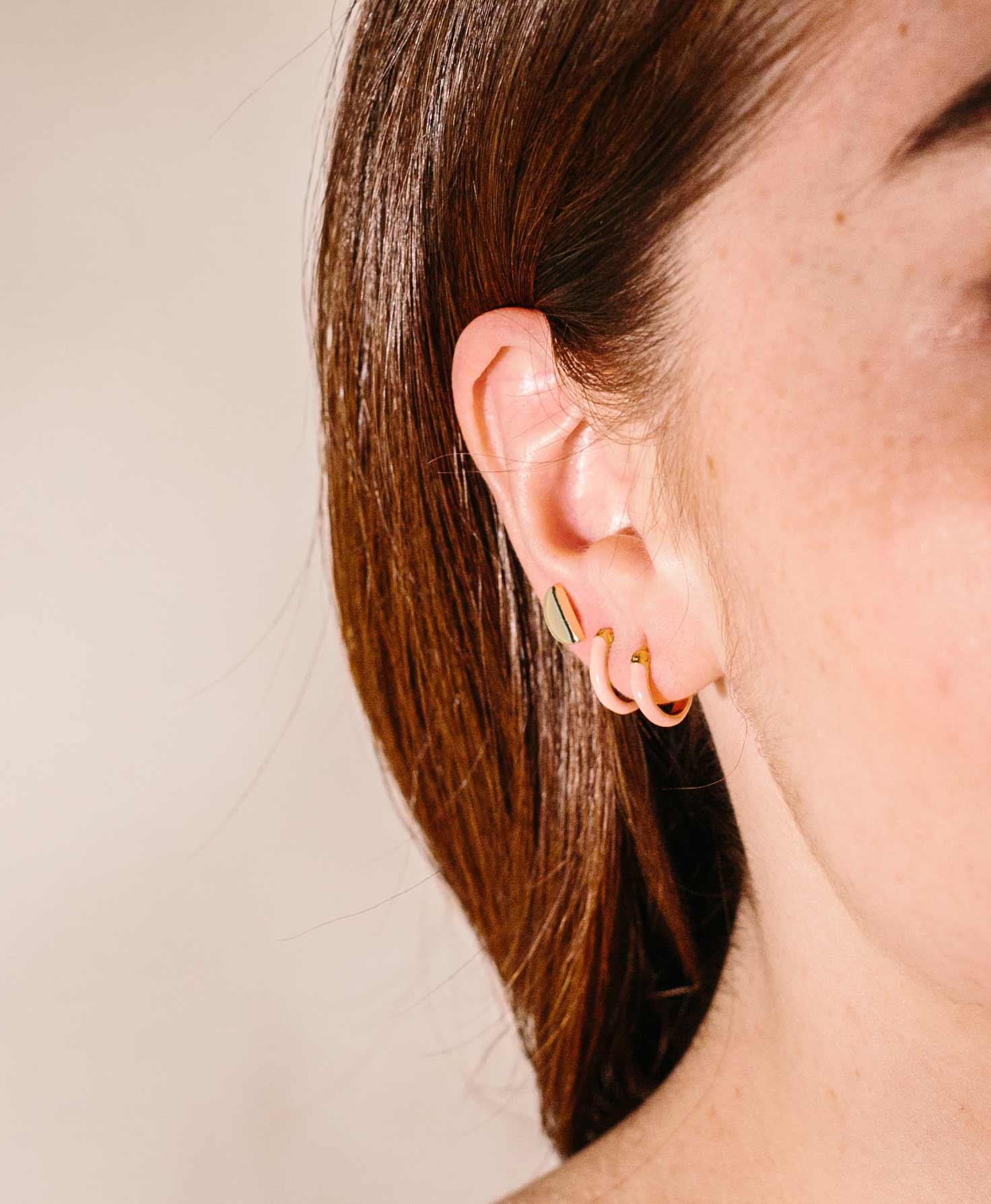 Half of a model's face is shown. On her ear, she wears three dainty hoop earrings. She wears two Golden Hour Hoop earrings on her lobe, and a simple golden halfmoon earring further up her ear.