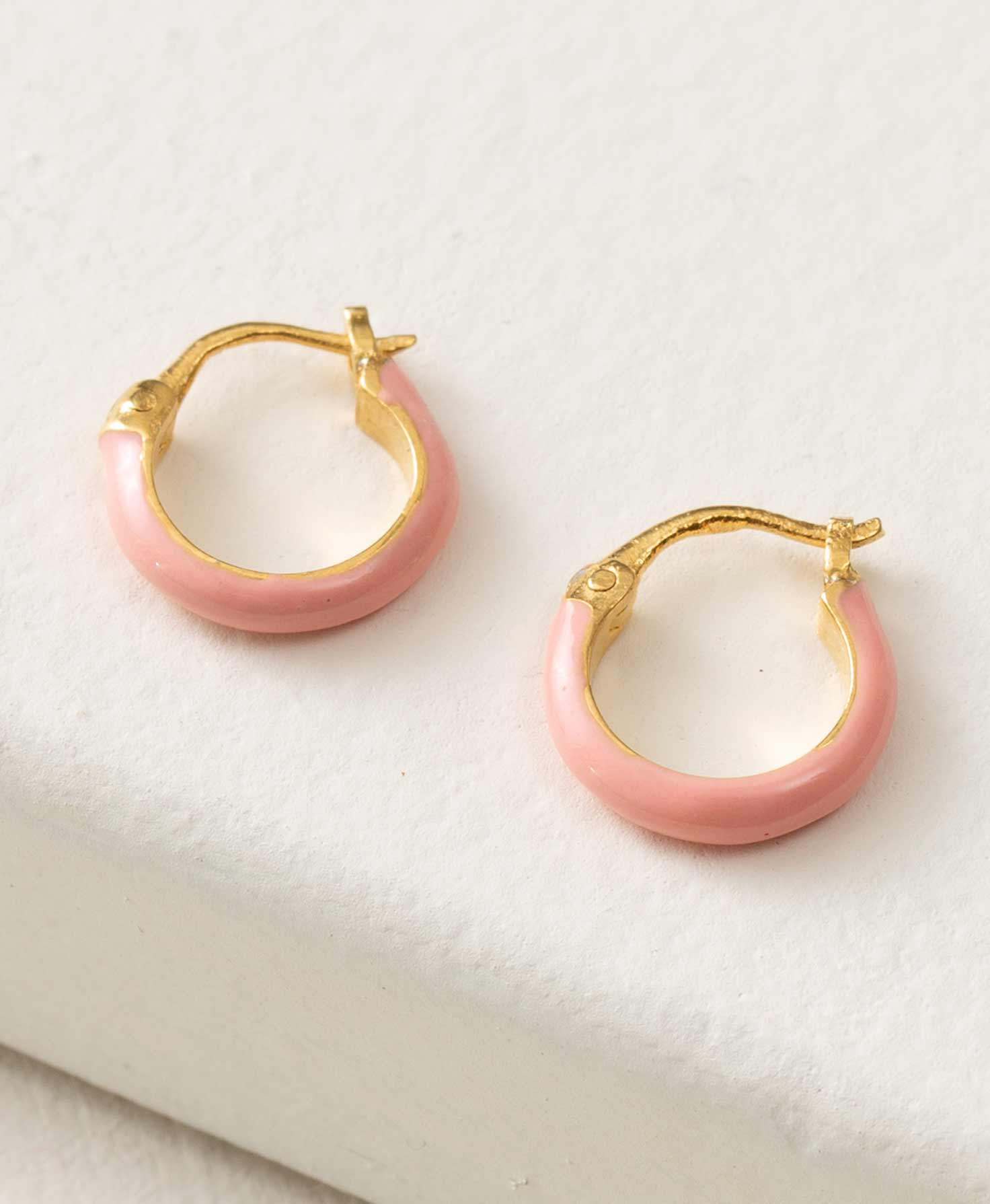 The Golden Hour Earrings are positioned on top of a white block. They are composed of a small gold hoop coated in smooth, blush-colored enamel. The earrings feature a latch-back style closure that snaps into place.