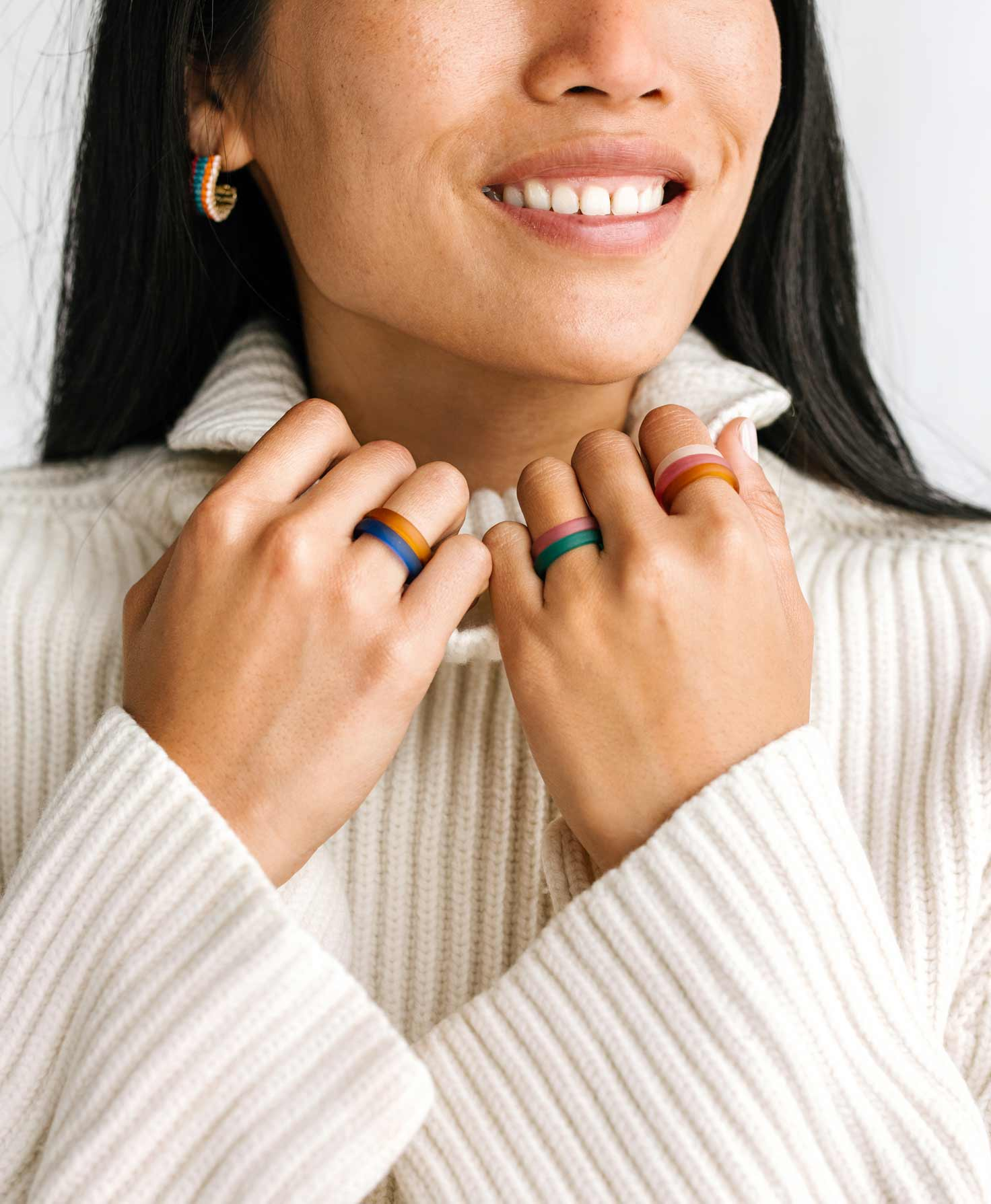 A model wears the Groovy Hoops and a white sweater. On her fingers, she wears an array of rings from the Glass Ring Bar in colors that complement the Groovy Hoops.