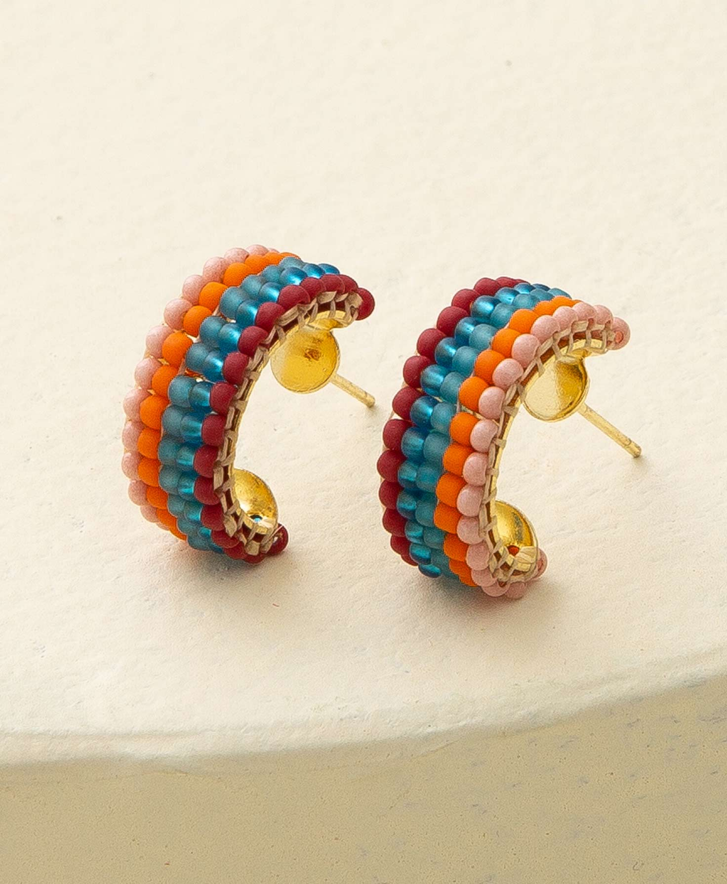 The Groovy Hoops sit on a cream-colored platform. A flat, wide brass hoop is accented with glass beads. The beads are arranged in lines that go around the entire hoop. The rows of beads are arranged as follows: solid blush, solid orange, solid teal, transparent teal, and solid maroon.