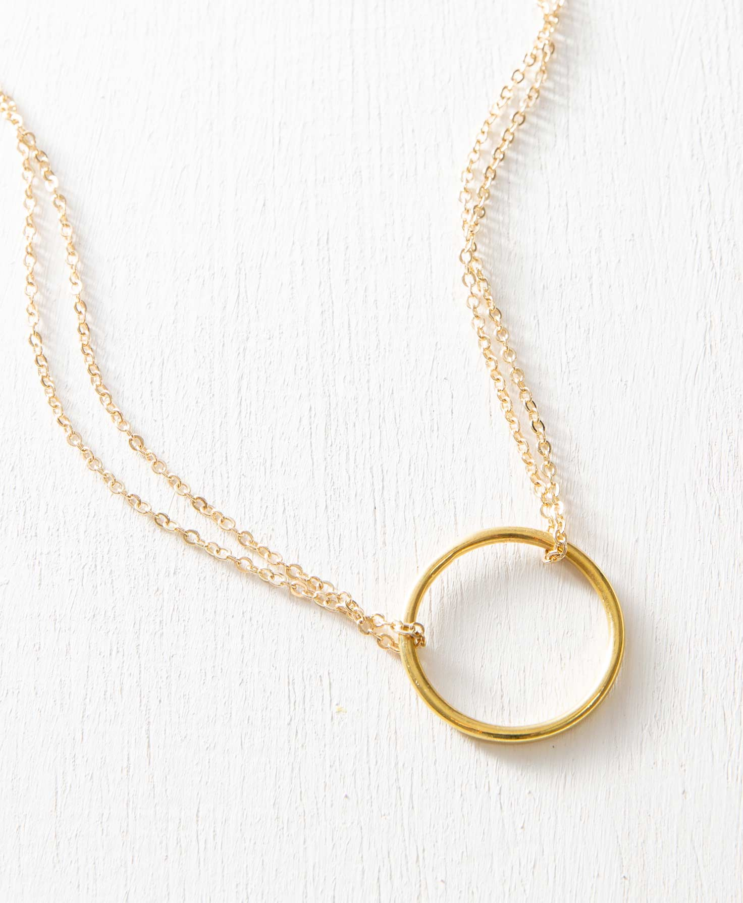 The Halcyon Necklace lays on a white background. The centerpiece of the necklace is a shining brass hoop pendant that is 1