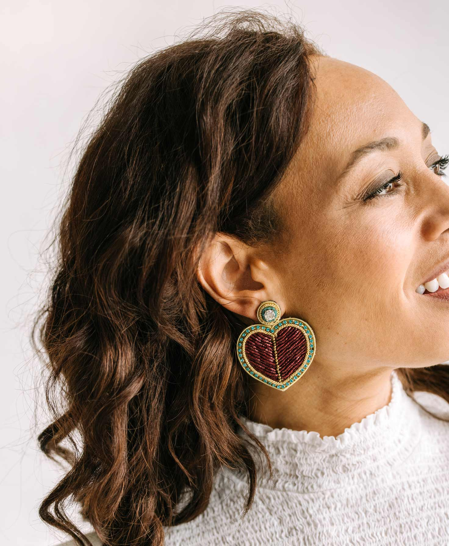A model wears the Heartstrings Earrings. They make a bold statement with their size and sparkle. The model pairs these statement earrings with a romantic white top.