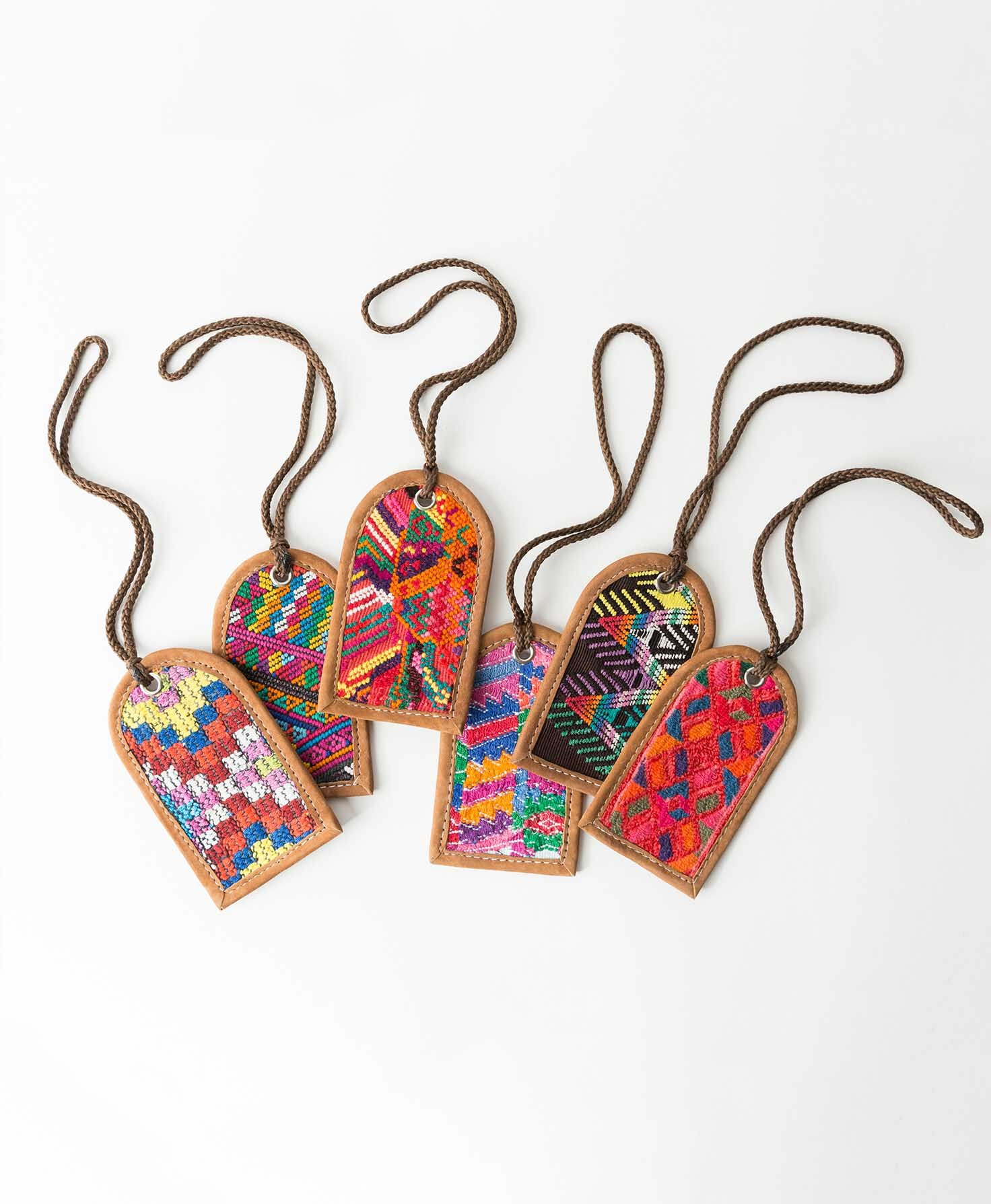 Six Huipil Luggage Tags lay on a white surface. Each features a different patterned woven textile. The color palettes vary, but most feature bright shades of pink, orange, red, blue, and purple.