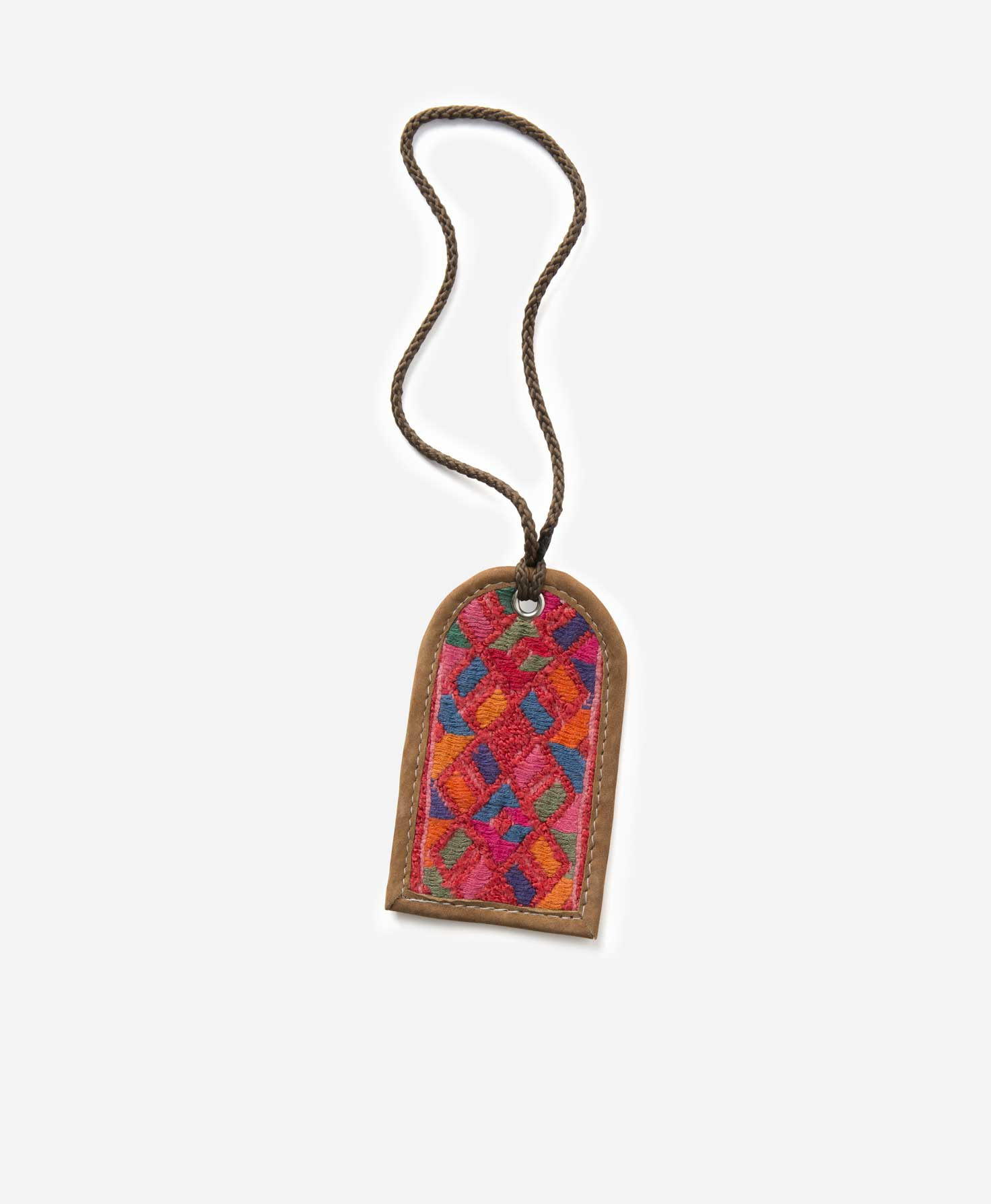 One Huipil Luggage tag lays on a white surface. The tag is shaped like a rectangle with a rounded top. The border is made of leather in a dark caramel shade, and in the center is a vibrant woven textile in a traditional Guatemalan pattern. The pattern and color of each tag varies, but all are bright and feature geometric patterns. At the top of the tag, a brown cord loops through the fabric, allowing the tag to be attached to a bag.