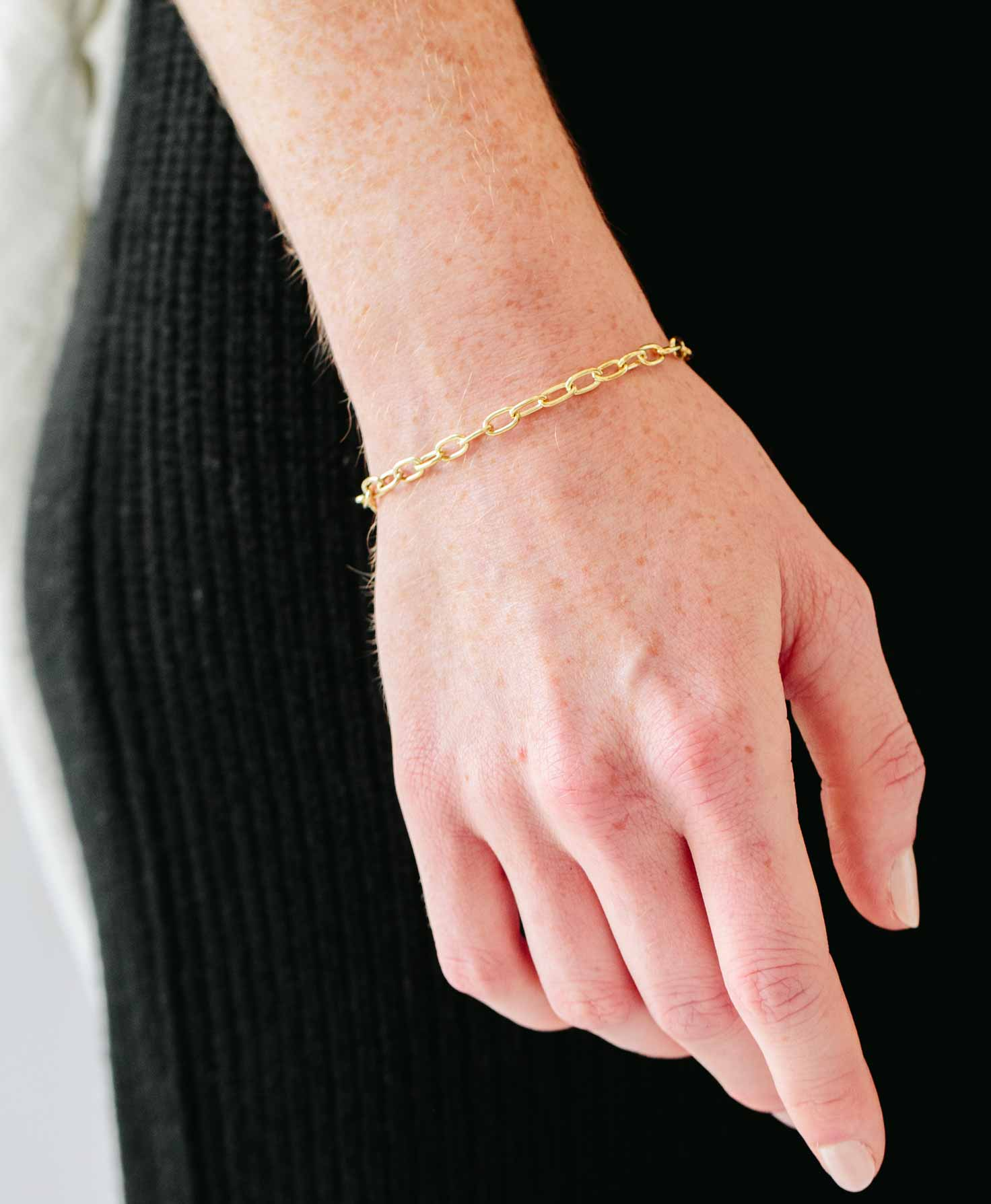 A model's arm is shown wearing only the Infinity Bracelet for a simple, luxe look.