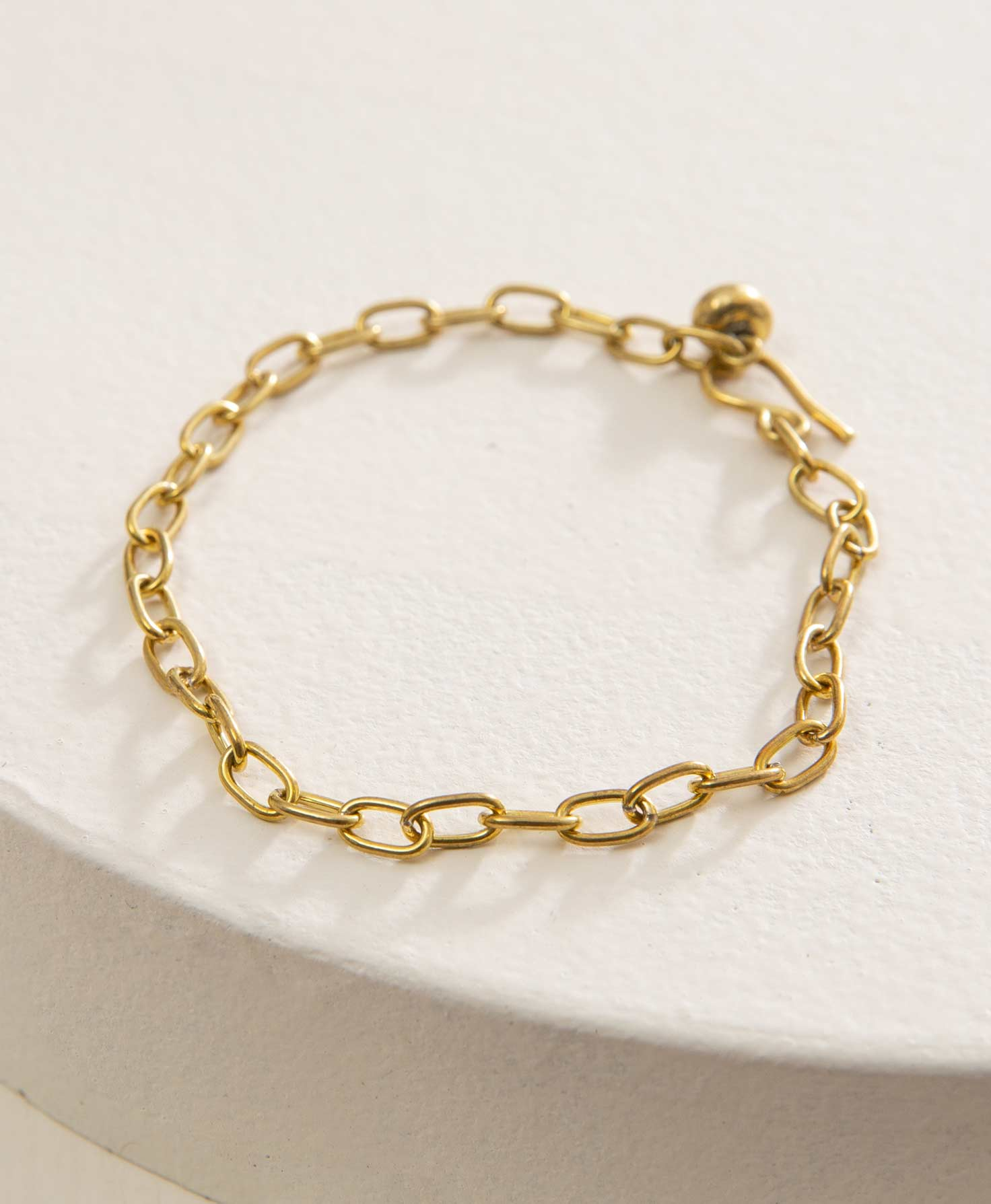 The Infinity Bracelet lays on a white surface. It is a simple chain-link style bracelet made entirely of shining brass. The links of the chain are oval shaped. At the back of the bracelet, a brass hook is shown looping through the final link in the chain, securing the bracelet in place. However, the hook can be linked through any of the chain links, making the bracelet adjustable.