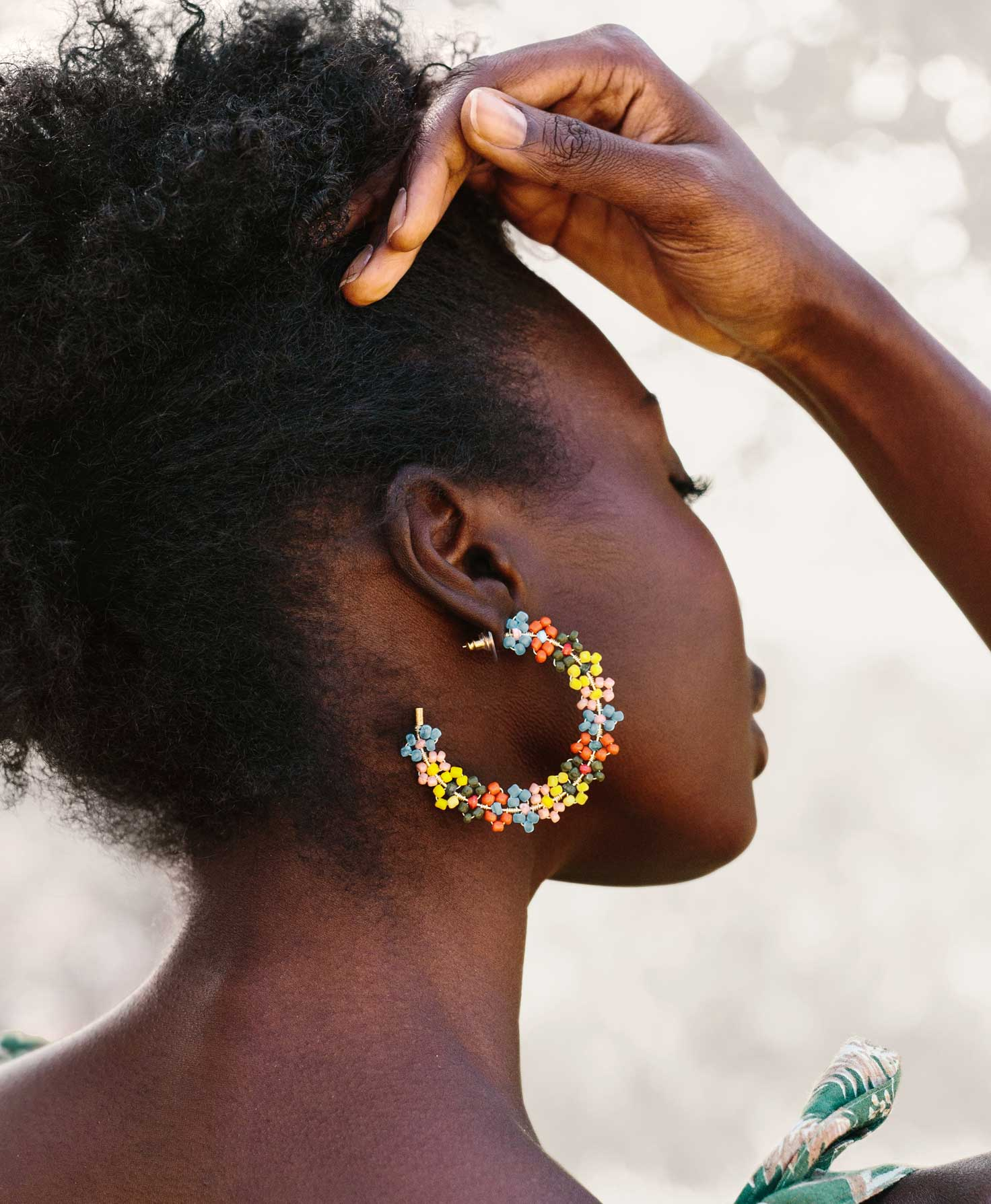 A model is shown with the side of her face towards the camera. The large silhouette and vibrant colors of her Lantana Hoops make for a bright statement.