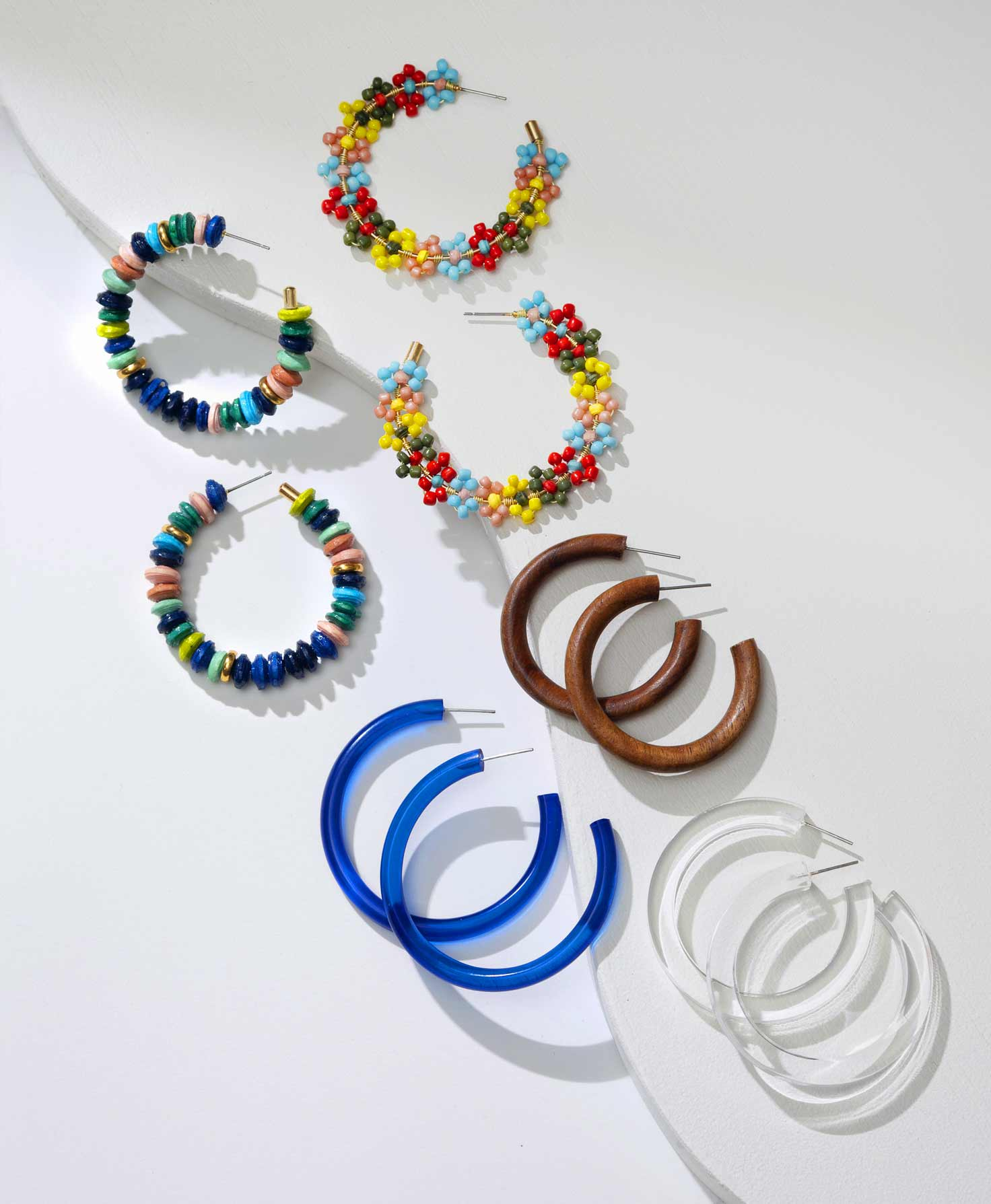 An Artisan's hands are shown assembling bright beads to make the Lantana Hoops. An array of different colored beads lay on the table below.