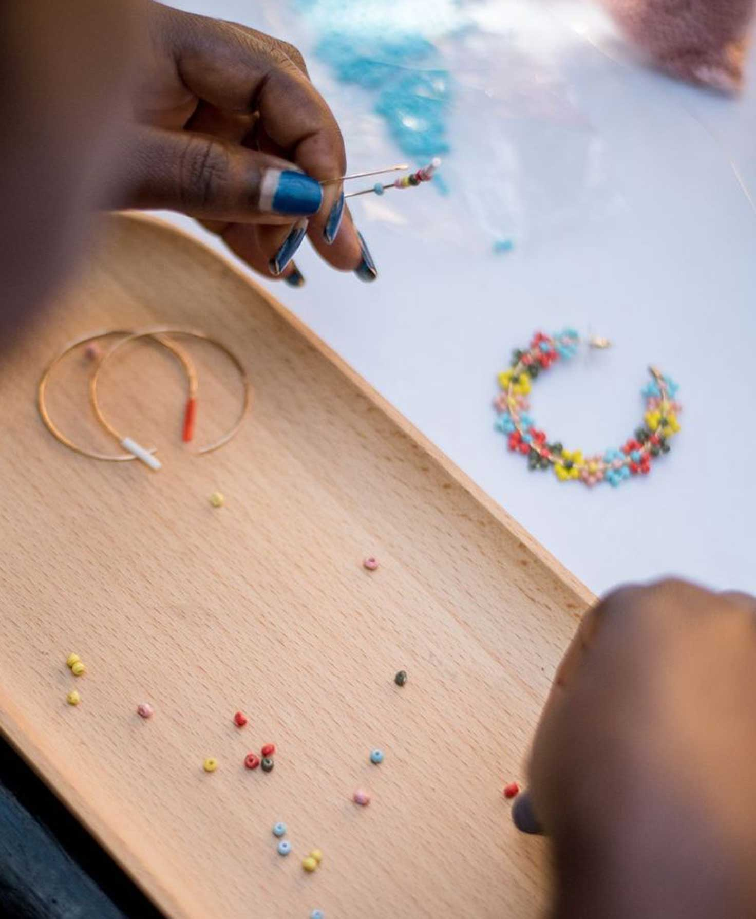 An Artisan's hands are shown close up. In her hands, she shows off a finished pair of the bright Lantana Hoops.