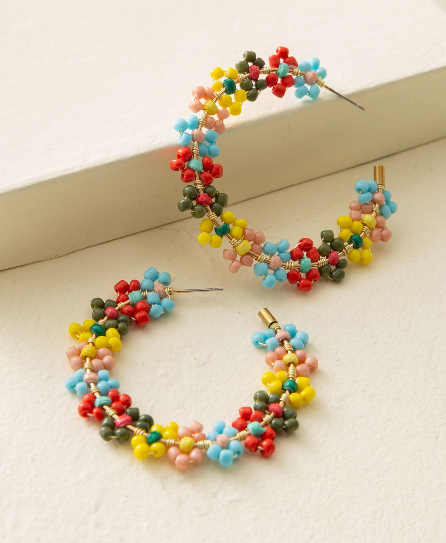 The Lantana Hoops lay against a cream backdrop. They are gold hoop earrings with flower designs arranged along the entire hoop. Each flower is composed of a colored paper bead in the center, with seed beads in a contrasting color forming the surrounding petals. The bead colors include olive, red, aqua, blush, yellow, and green. The flowers are arranged so that they lay flat along the outside of the hoop.