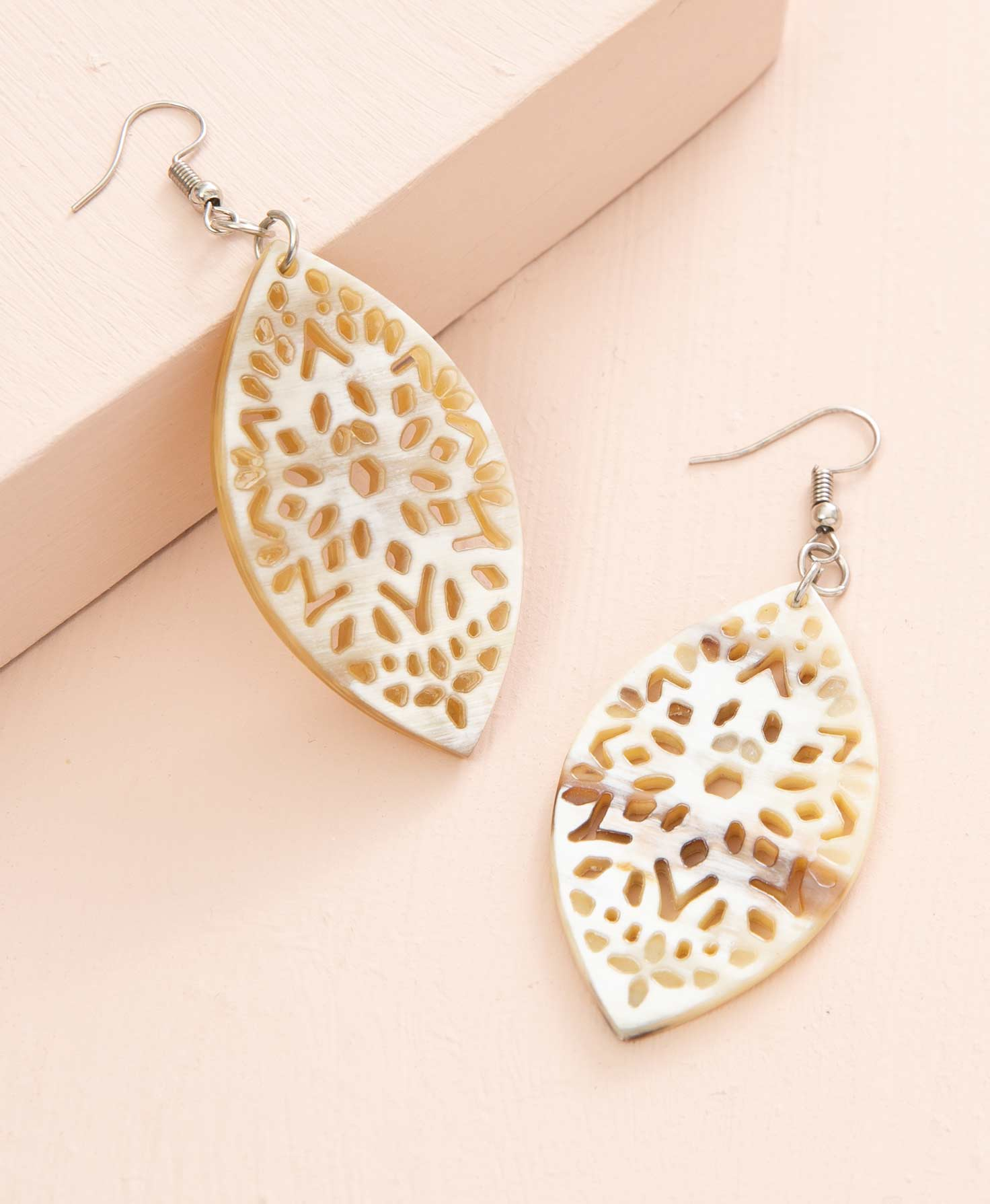 The Lovely Lace Earrings lay on a peach colored background. They are almond-shaped and are made from pieces of natural horn featuring laser-cut designs. The intricate pattern of the cut-outs gives the pair a lace-like feel. The horn is cream-colored but features natural variations and markings that are unique to each pair. The ear hooks are silver.