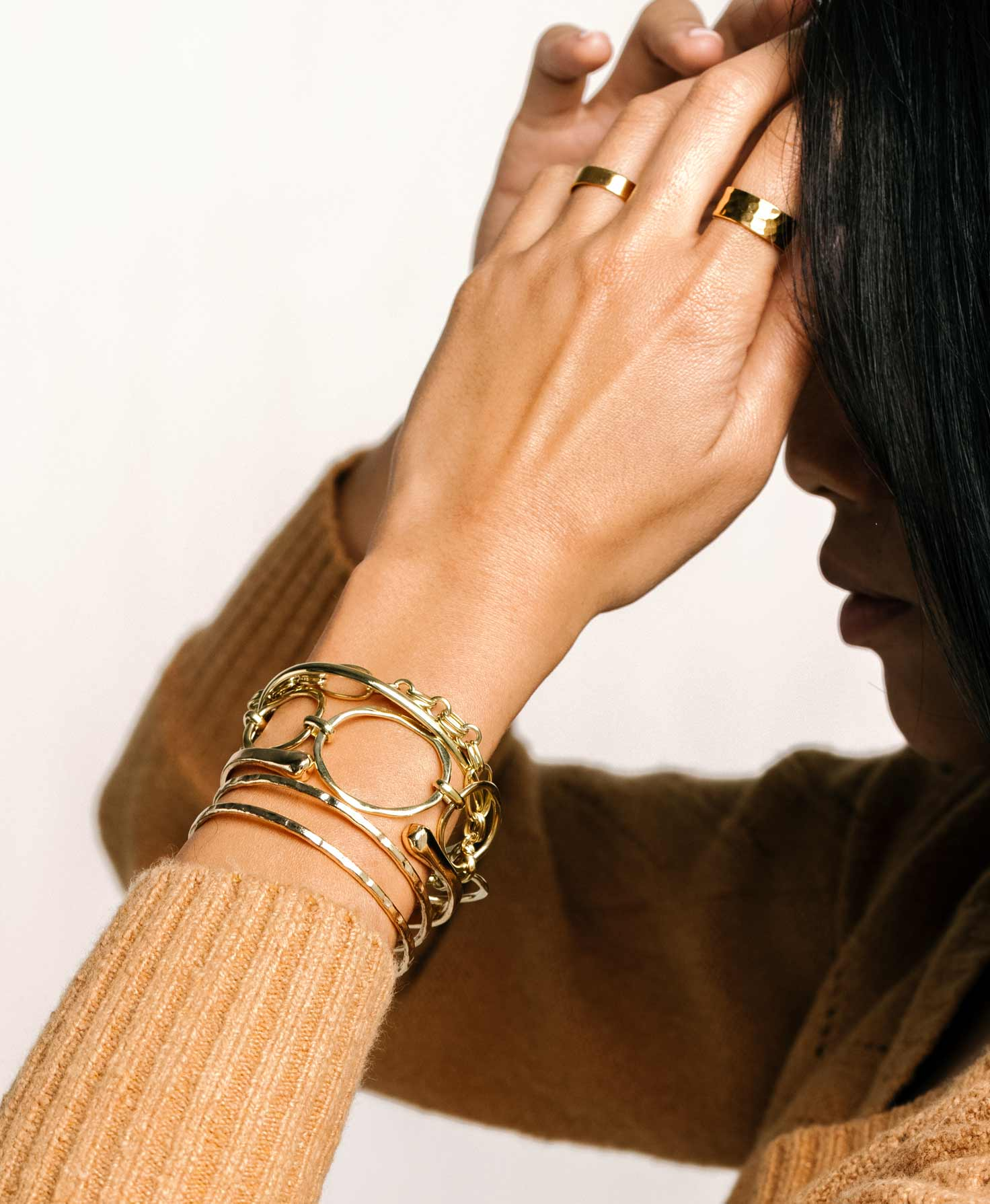 A looping video shows a woman's arm with a stack of shining golden bracelets, including the Shindig Bracelet, Pathway Bracelet, Loyalist Cuff, and Open Space Cuff.