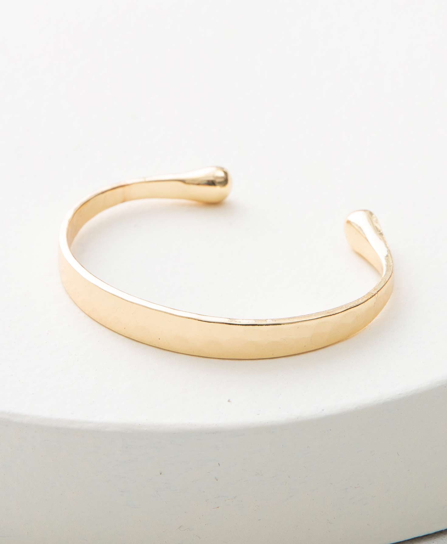 The Loyalist Cuff sits on a white platform. It is made of shining gold plated brass and has a minimal design. The cuff is thin and flat, with no embellishments or markings. There is an opening at the back where it can be slid onto the wrist. At either end of the cuff, the metal is formed into a ball shape.