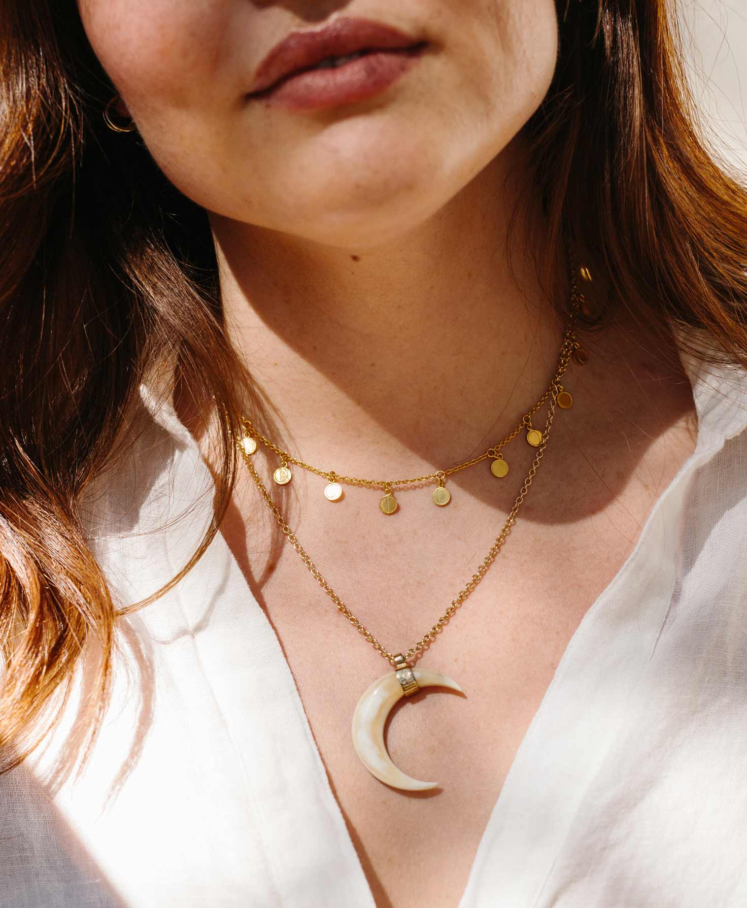 A model wears a silky white top with a v-neck. She wears the golden Lunar Necklace with the longer Mystic Moon Necklace. The two necklaces together create a celestial, magical look.