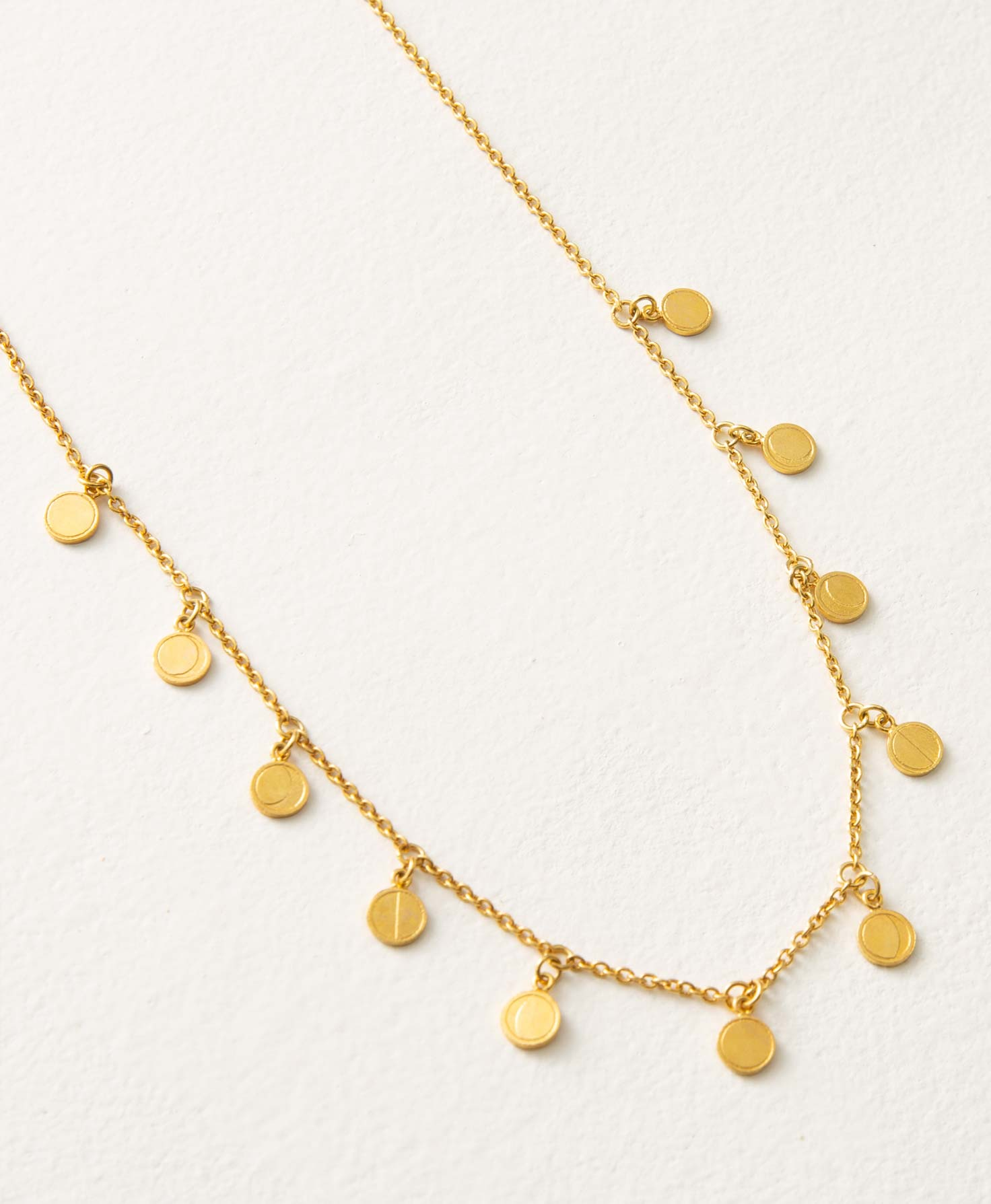 The Lunar Necklace lays flat on a white background. It consists of a short gold chain accented with 11 small, shiny golden discs. The discs are attached to the chain via jump rings so they remain in a fixed position, and are spaced roughly an inch apart. Each disc features a minimalistic etched design of a different phase of the moon.