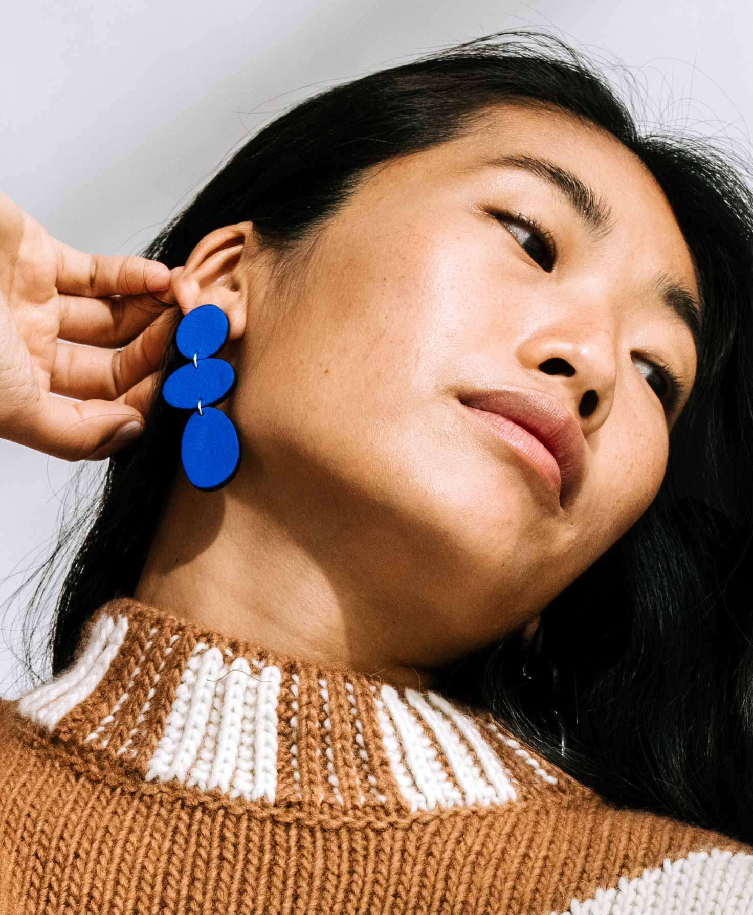 A model wears the Lupine Earrings. Their length and bright cobalt color make them stand out against her neutral tan dress.