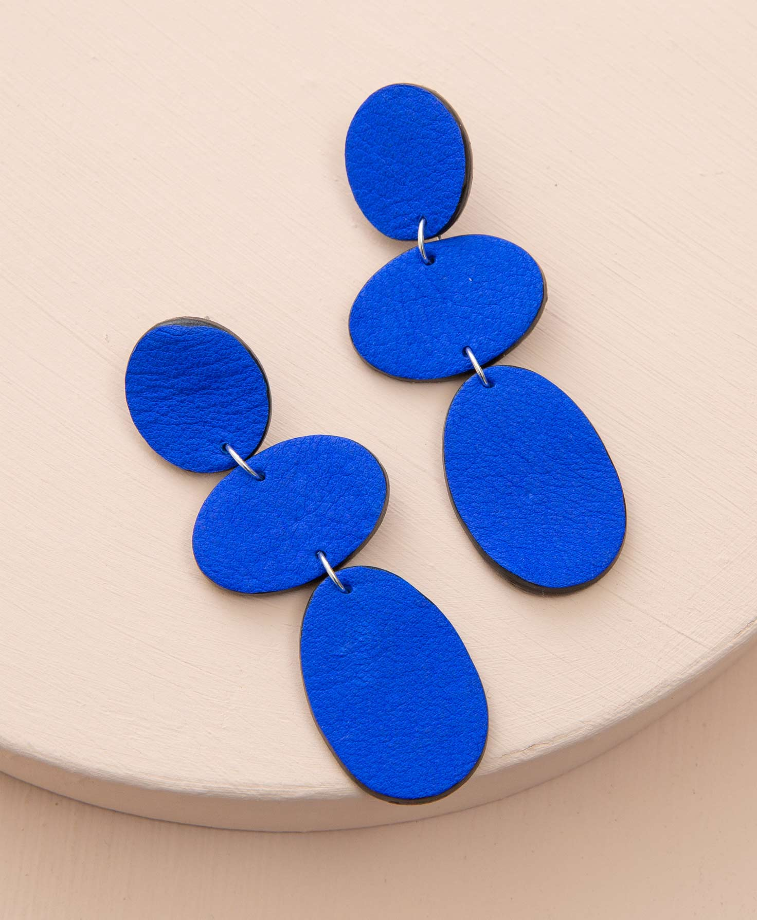 The Lupine Earrings sit on a cream-colored platform. They are post-style earrings made of bright cobalt blue leather. At the top of the earring is a circular leather piece. Connected to this via a silver jump ring is a horizontal oval leather piece. Below this is a vertical oval leather piece.