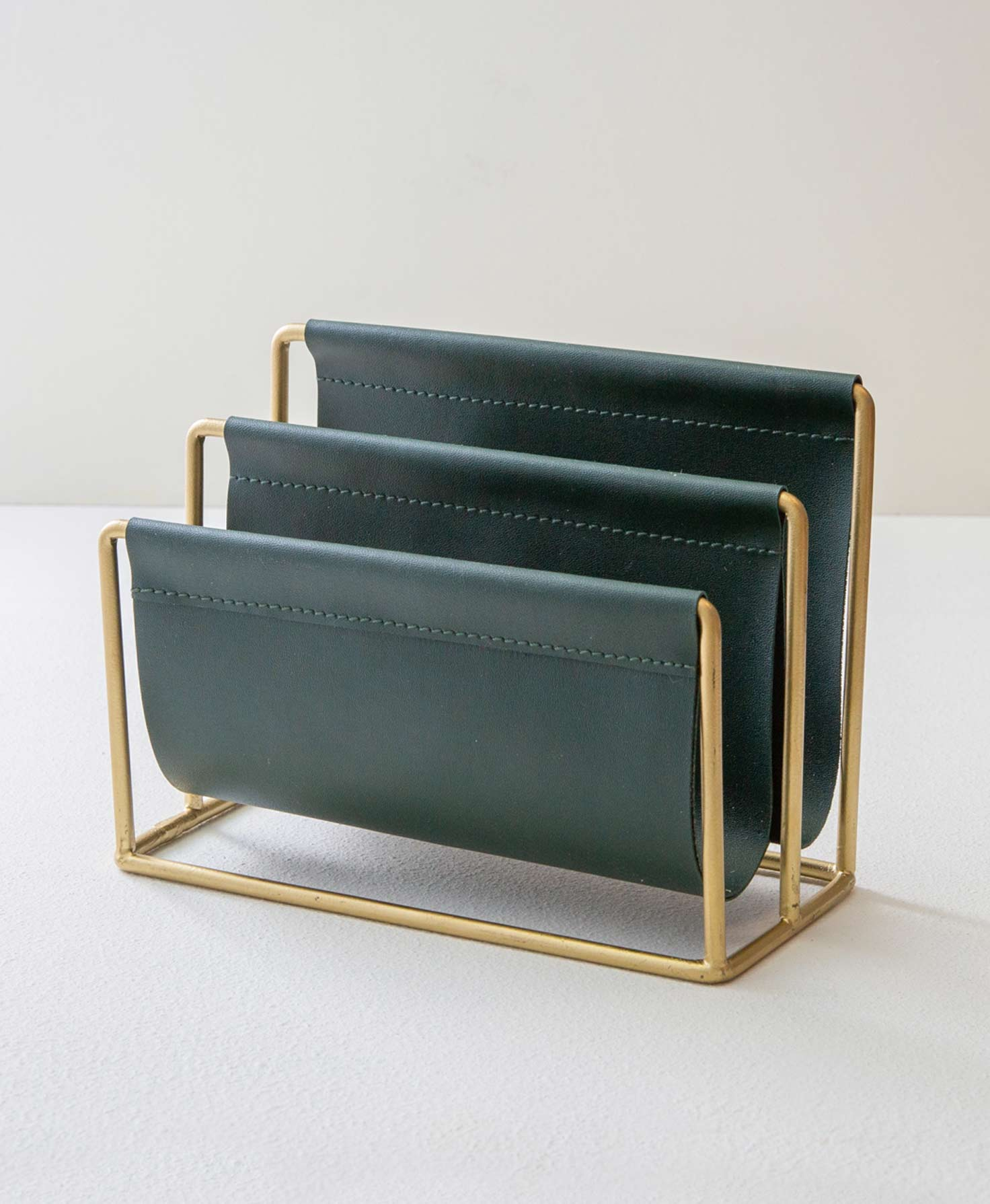 The Mail Caddy sits on a white background. It is composed of a brass-colored metal frame that forms two sections for holding mail. Deep green faux leather is attached to each metal bar and hangs down to form a place for mail to rest. The front section is lower than the back section so that the height of the mail is staggered.