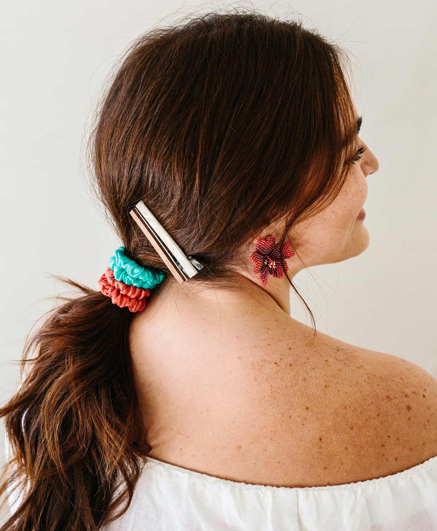 A model is shown with her back to the camera. She wears her hair in a ponytail, tied with the coral and aqua Mainstay Scrunchies stacked on top of each other. Above the scrunchies, she wears two of the Earth Tone Hair Clips stacked on top of one another.