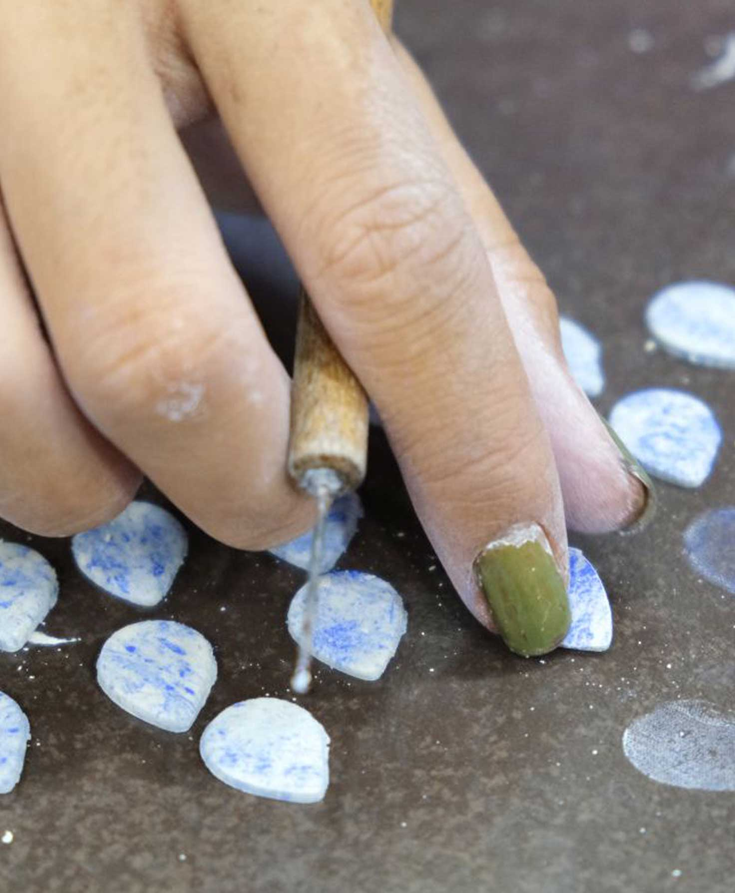 A model's hand is shown carefully applying the gold luster to the bottom of the Marbled Sky Studs.