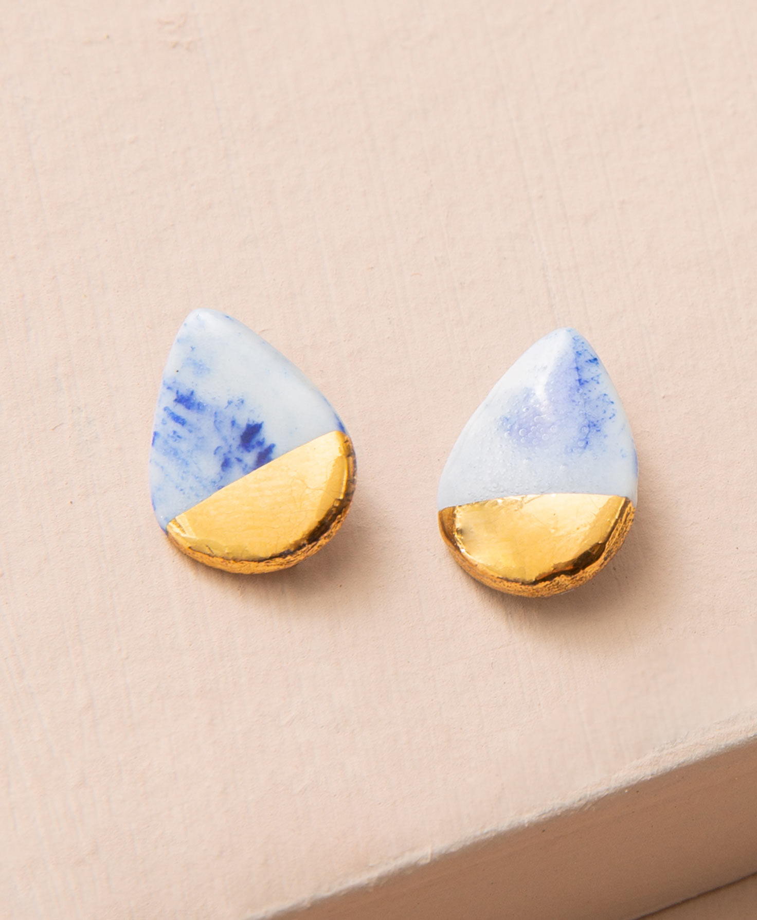 The Marbled Sky Studs lay against a peach colored background. They are dainty teardrop-shaped studs made of porcelain. The main body of the earring is white with cobalt blue markings, resembling a classic china pattern. The markings of each earring vary. The bottom of the earring is dipped in gold luster for a shining accent.