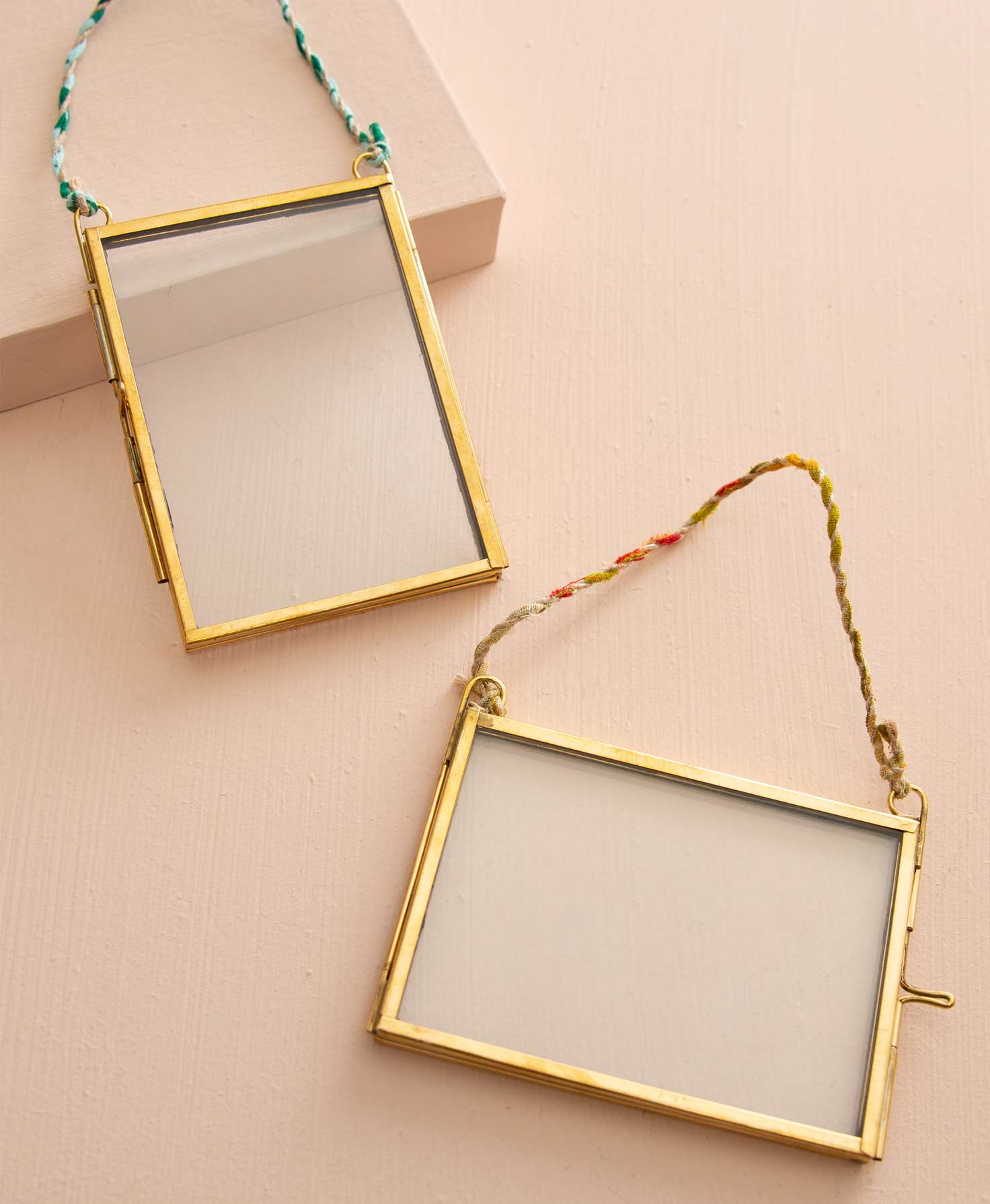 The two frames included in the Memento Frame Ornaments set lay on a peach background. Each of the glass frames is outlined in shining brass. Both frames are rectangular, but one is oriented vertically and the other horizontally. On one edge of each frame, a mechanism enables the brass frame to open so that a photo may be placed between the glass and the frame. A twisted cord made of multicolor fabric is connected to the top corners of each frame, allowing them to be hung.