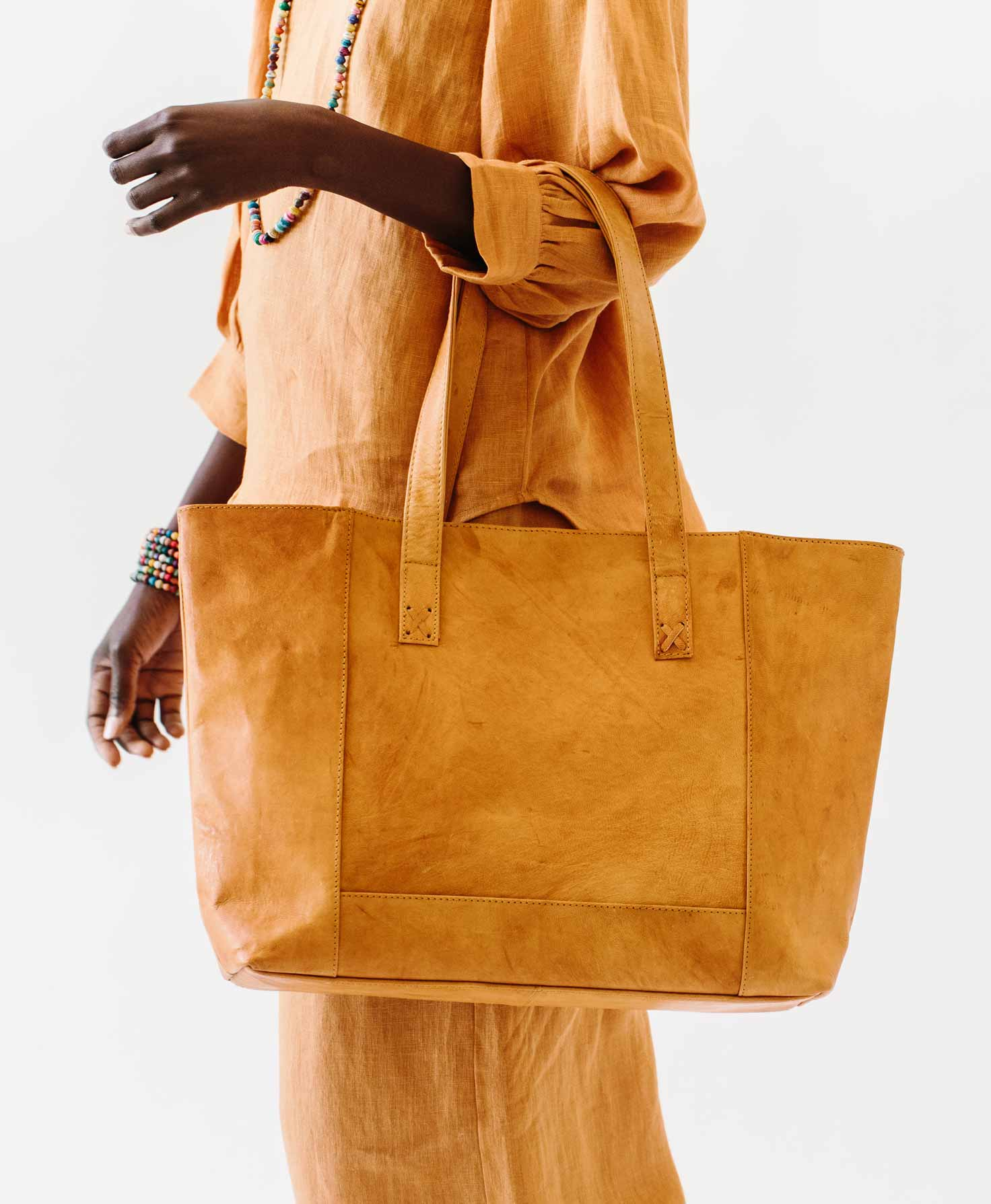 A model wears the Modern Leather Tote in the crook of her arm. The substantial looking bag has the light fawn color common to newer bags.