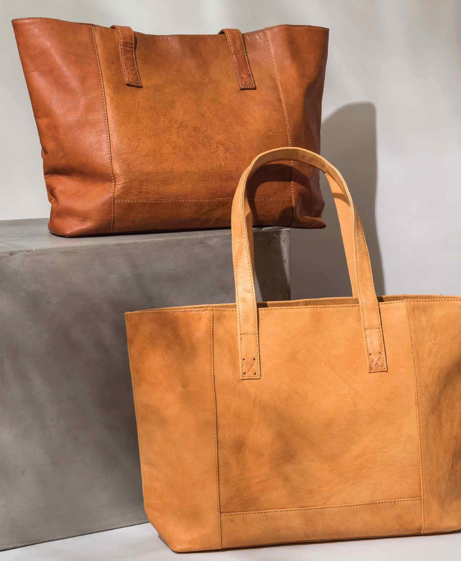 The Modern Leather Tote hangs against a white wall. It is a rectangular tote that is wider than it is high. The is a rectangular panel, allowing the bag to sit flat on its bottom. It is made of smooth, glossy, caramel-colored leather. There are some subtle natural markings and variations within the leather. The tote has a minimal design with no exterior pockets. There are two leather handles attached to the top of the bag, stitched onto the body of the bag with a small leather X.