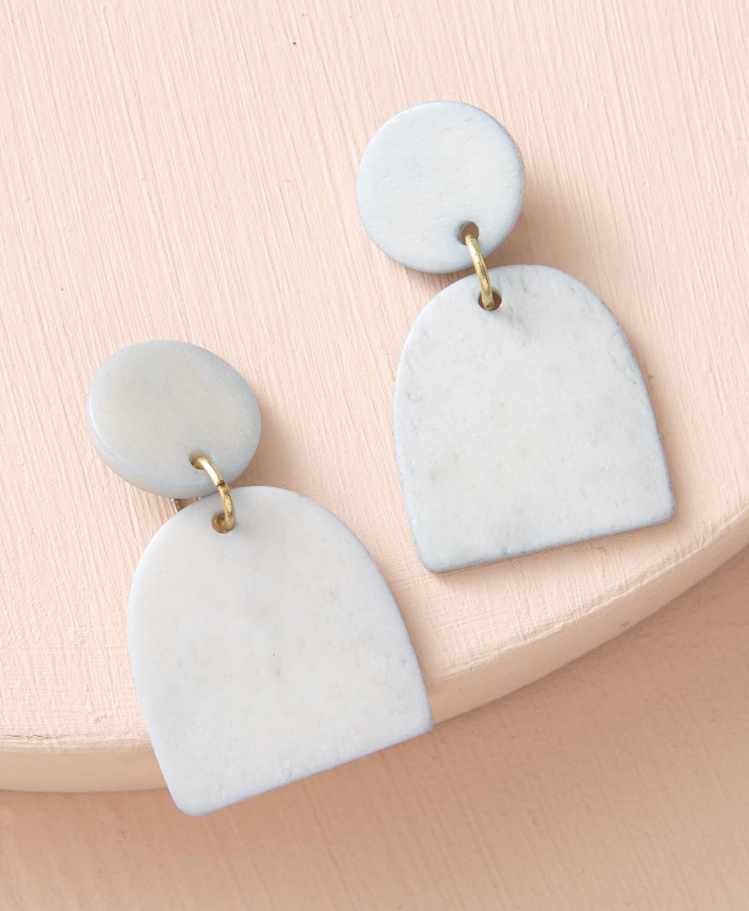 The Monument Earrings lay on a peach-colored surface. They are post-style earrings featuring geometric shapes carved from white bone. Attached to the stud is a white disc. Connected to this disc via a brass jump ring is a white shape that is curved on the top and flat on the bottom, resembling an oval cut in half.