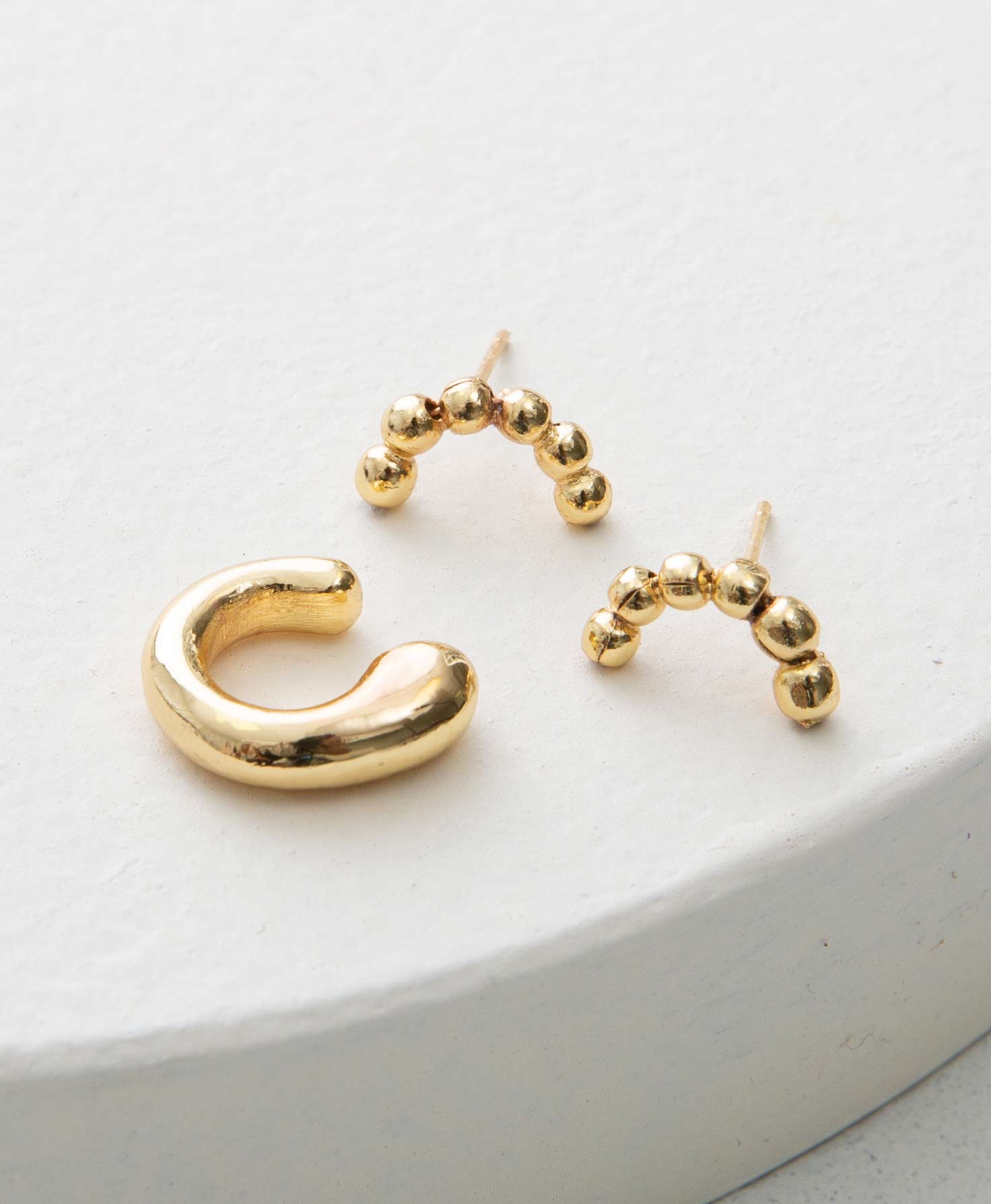 The earrings and ear cuff included in the Nebulous set sit on a white platform. The earrings are studs. They are composed of a row of brass balls that form an arch shape. The ear cuff is made of thick, shining brass. It has rounded edges and wraps around to form a C shape that is worn over the top of the ear.