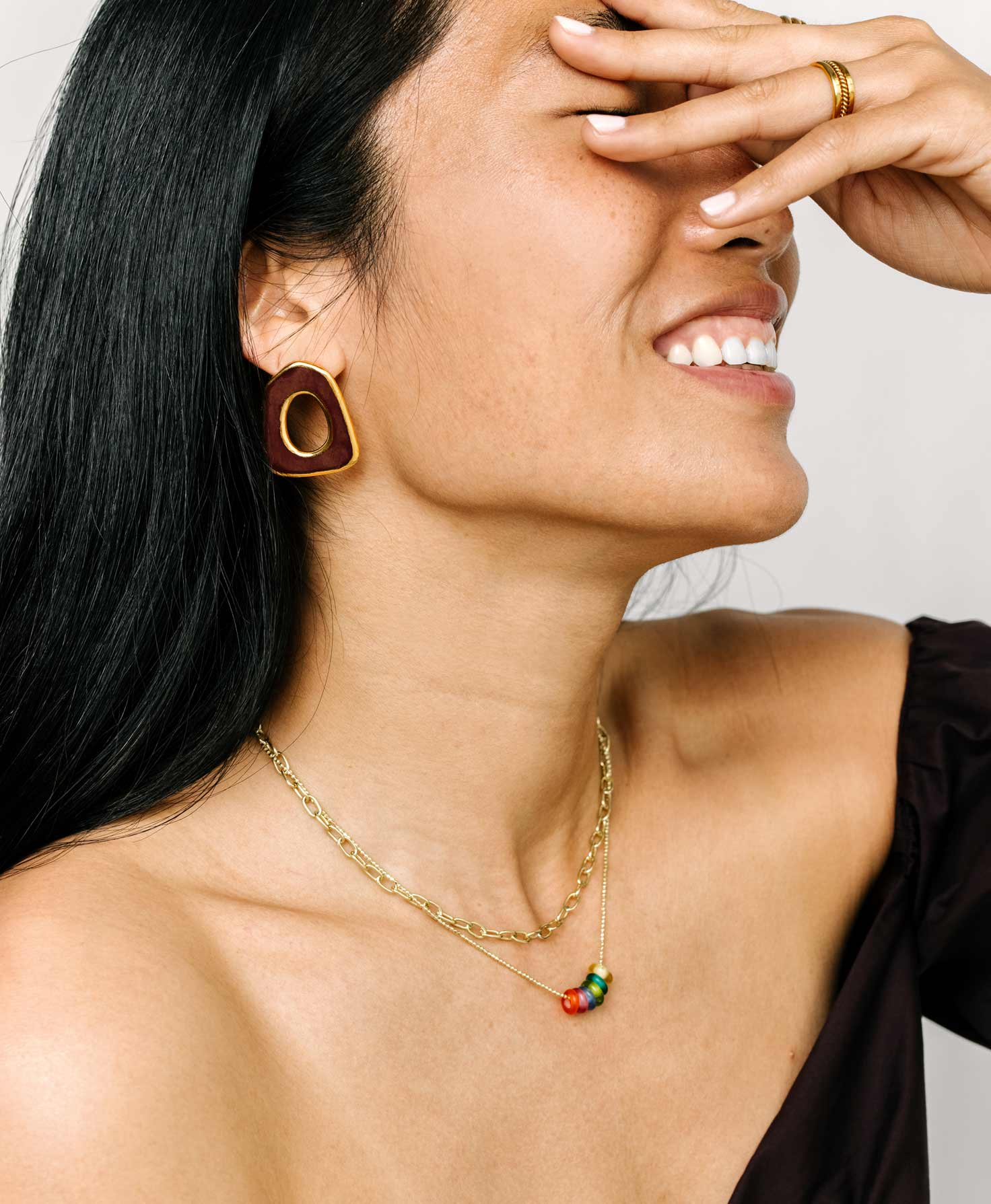 A model wears the Orb Necklace layered with the Infinity Necklace, another gold chain necklace. She finishes her look with the gold-rimmed Mesa Earrings.
