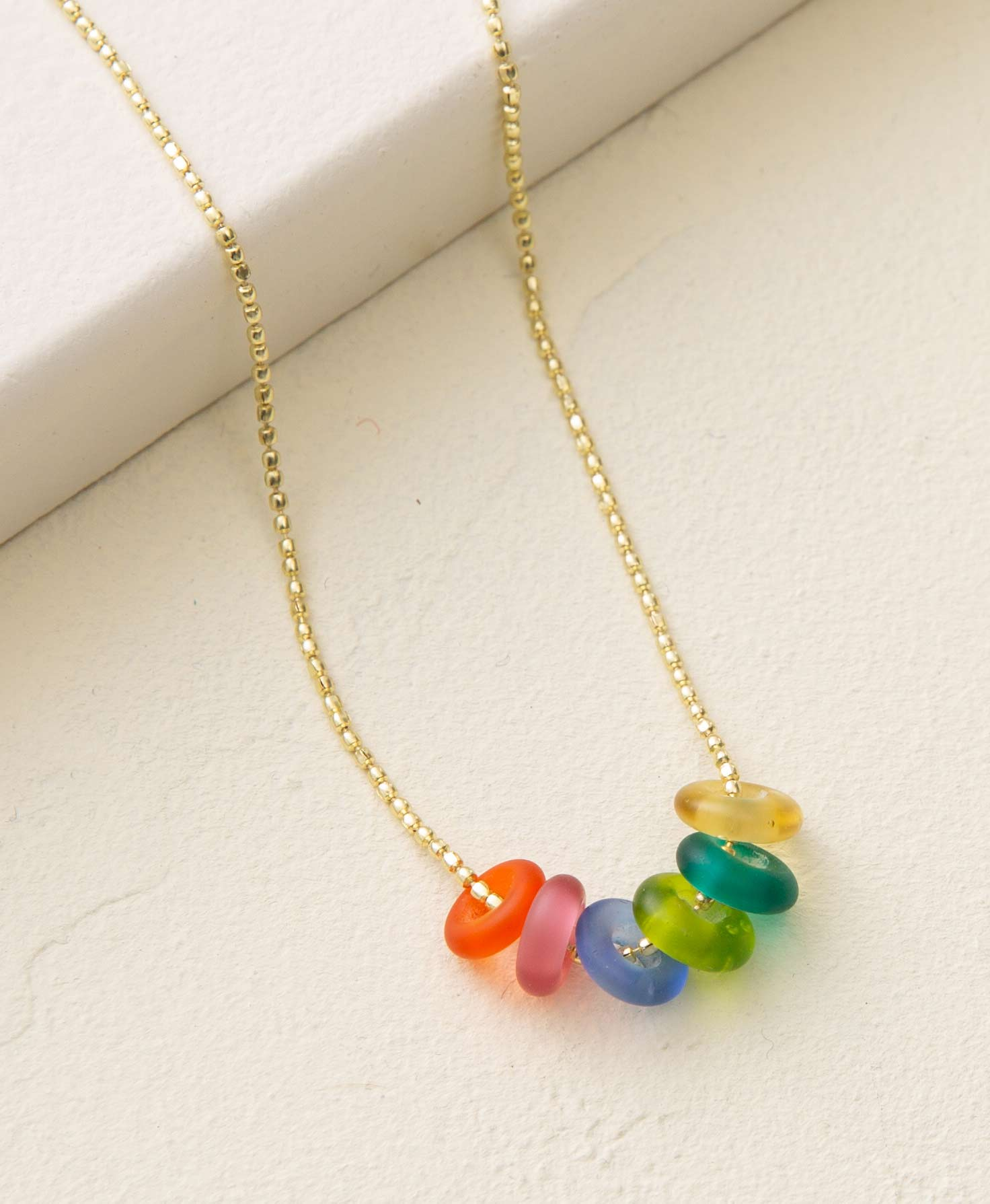 The Orb Necklace lays on a cream-colored surface. It has a dainty gold, ball-style chain. Strung onto the chain are six small, doughnut-shaped glass beads. The colors of the beads are: orange, pink, blue, lime, green, and yellow. They are semi-transparent and resemble sea-glass.