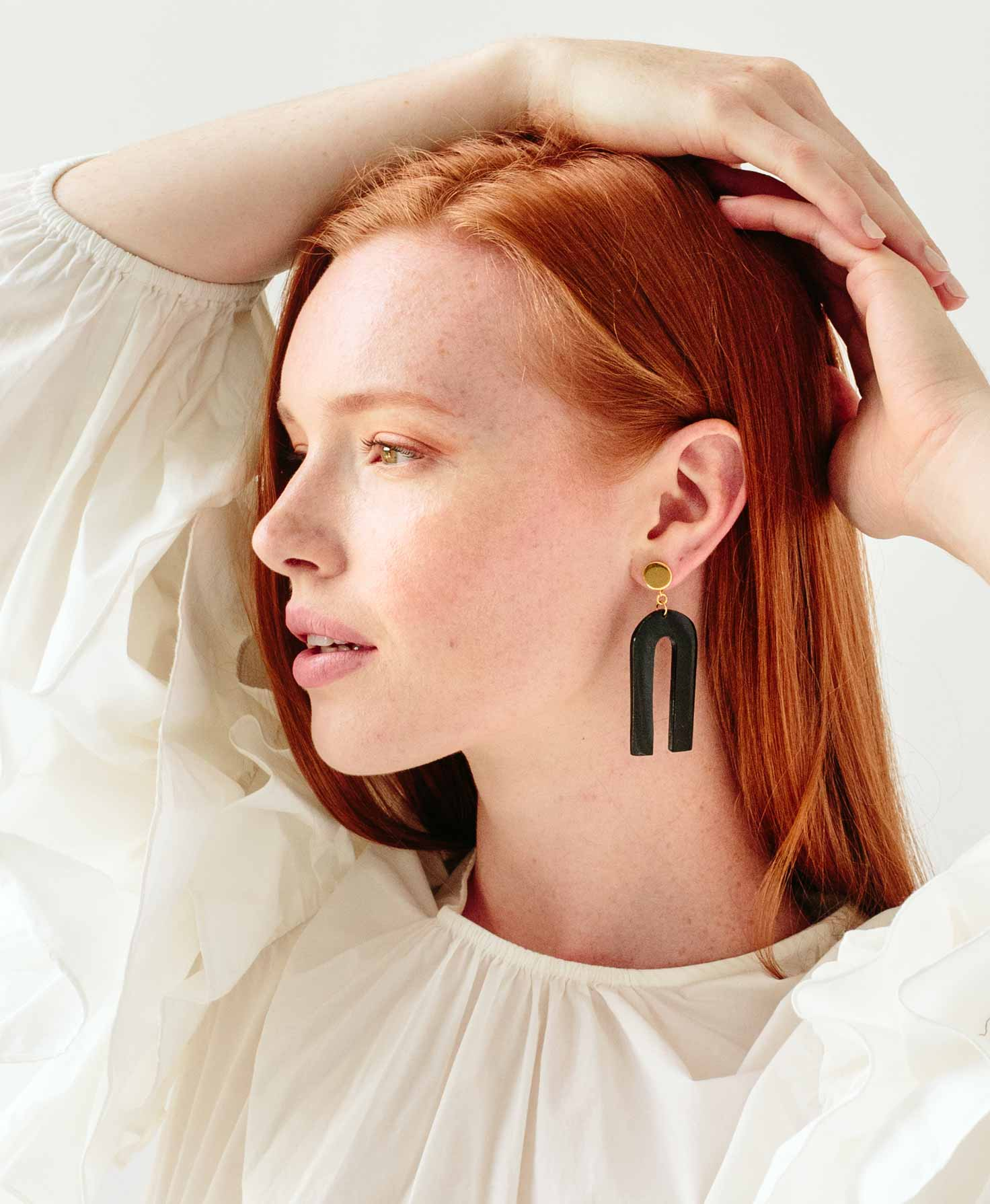 A model wears the Orleans Earrings. The earrings hang down several inches and make a modern statement when paired with her flowy white blouse.