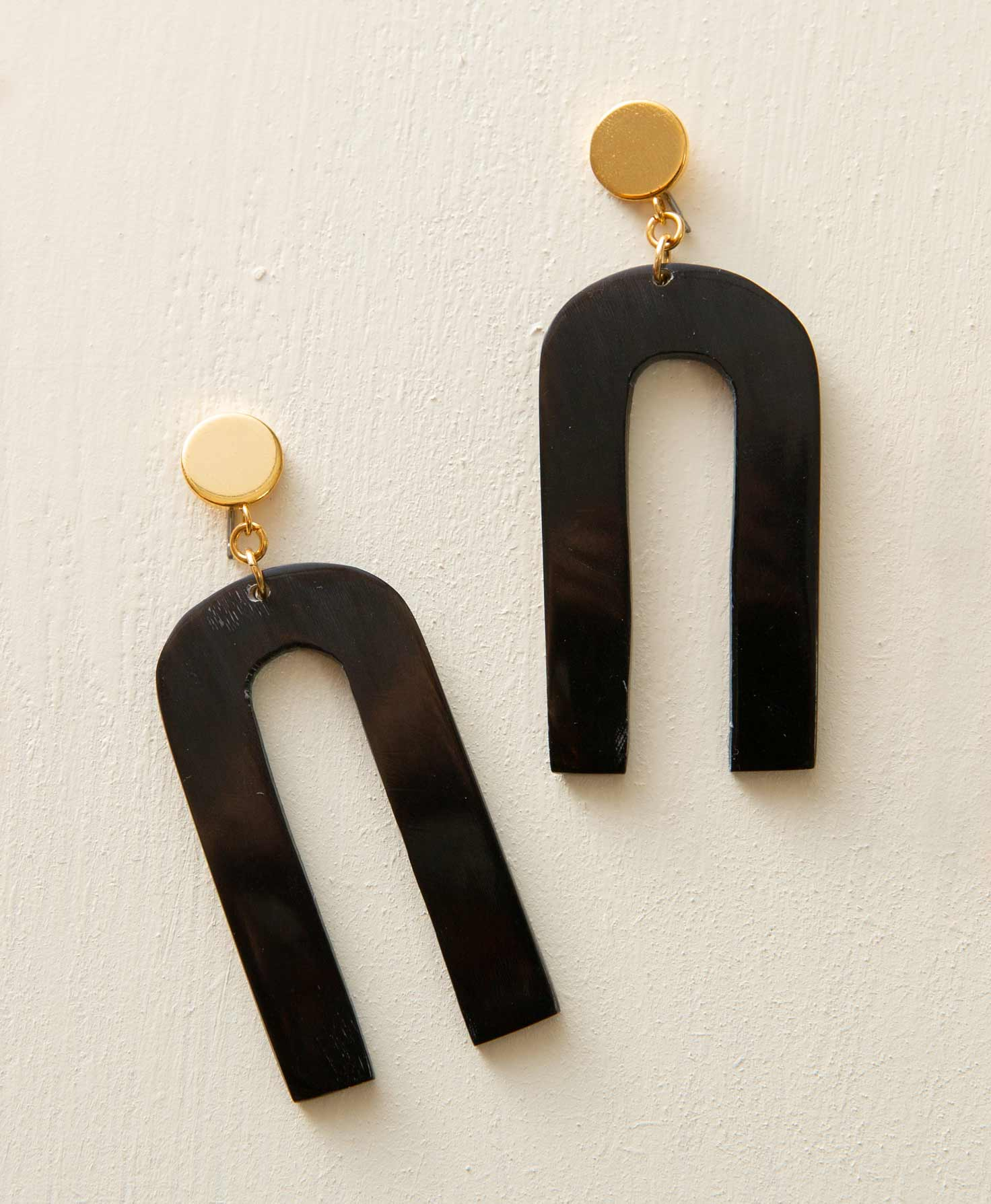 The Orleans Earrings lay on a white surface. They have a flat, round gold post. Swinging down from the post is a black horn piece shaped like an elongated arch. The pair has a modern, geometric look. The metal posts are glossy, and the black pieces have a matte finish.