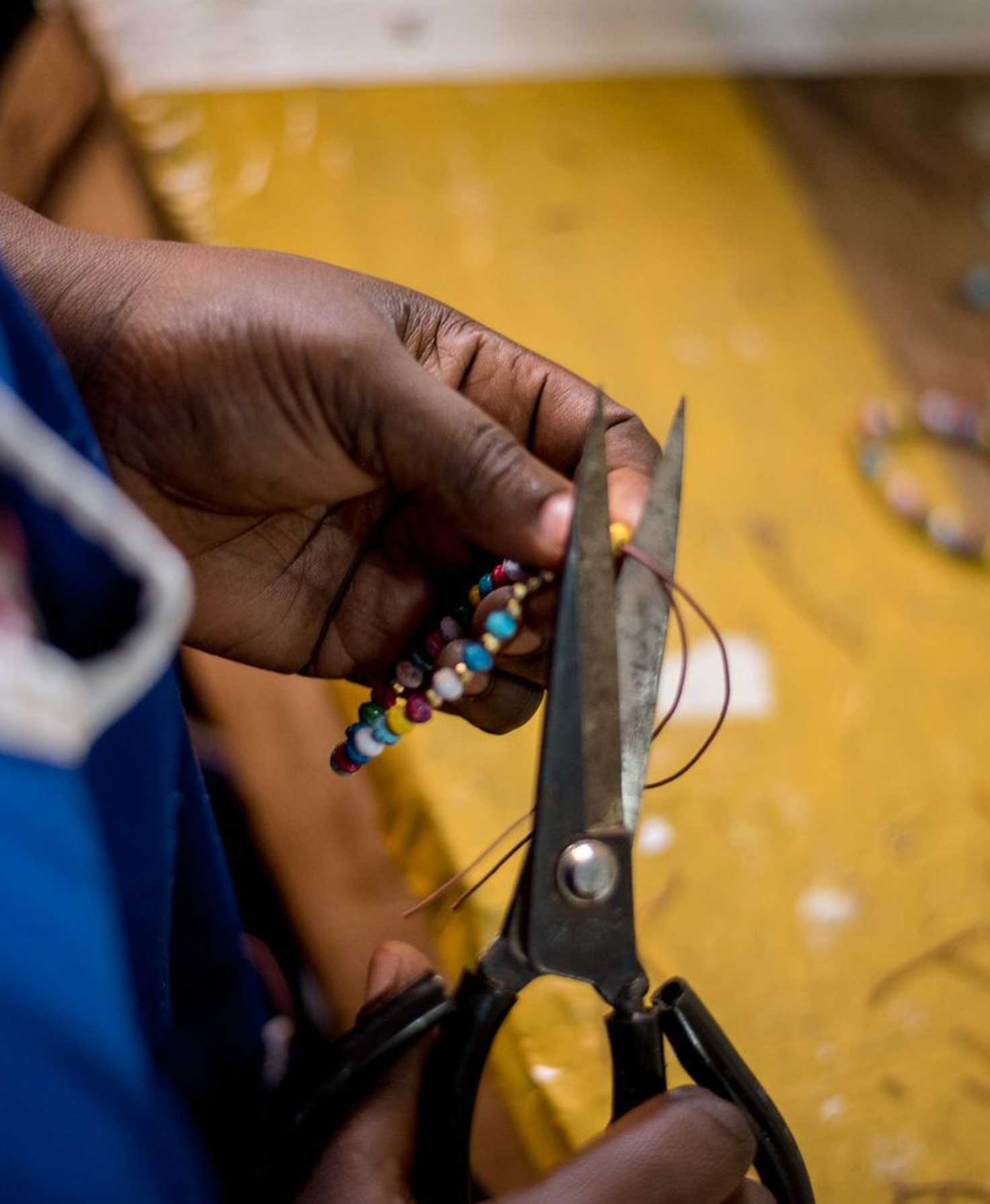 An Artisan sits at a table in a workshop. She smiles brightly at the camera as she shows off the bracelet she is working on. An array of brightly colored beads are strewn on the table in front of her.