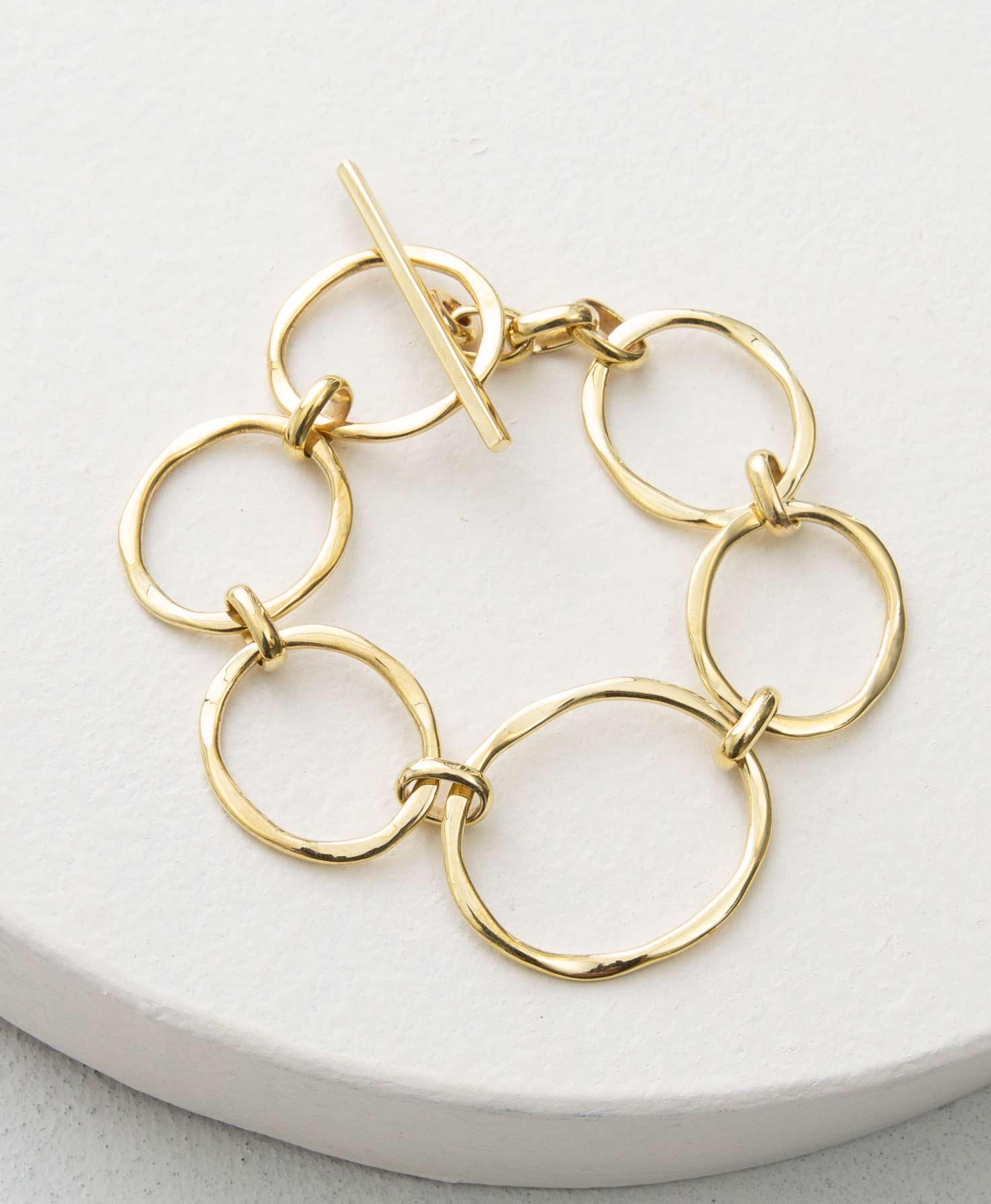 The Pathway Bracelet rests on a white platform. It is composed of six shiny brass hoops connected via small brass links. The hoops vary in size and have a hammered, organic look. At one end of the bracelet is a brass rod that goes through one of the hoops to secure the bracelet.