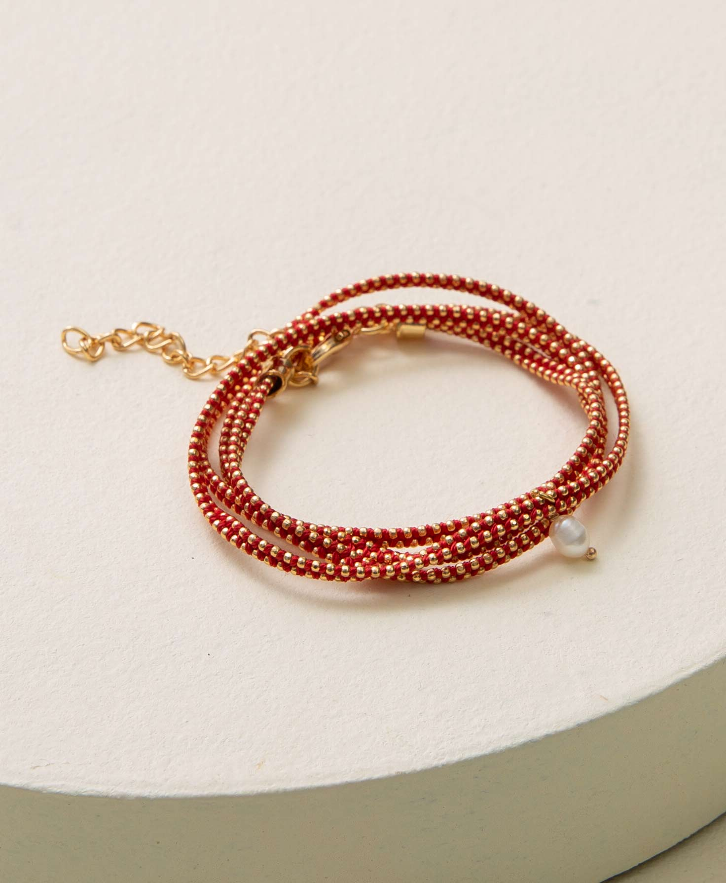 The Peacemaker Wrap Bracelet lays coiled on a white platform. It is composed of two layers of tiny brass beads wrapped in bright red thread. A pearl bead dangles from the center of the bracelet. A lobster-claw closure connects to a brass chain to secure the bracelet.