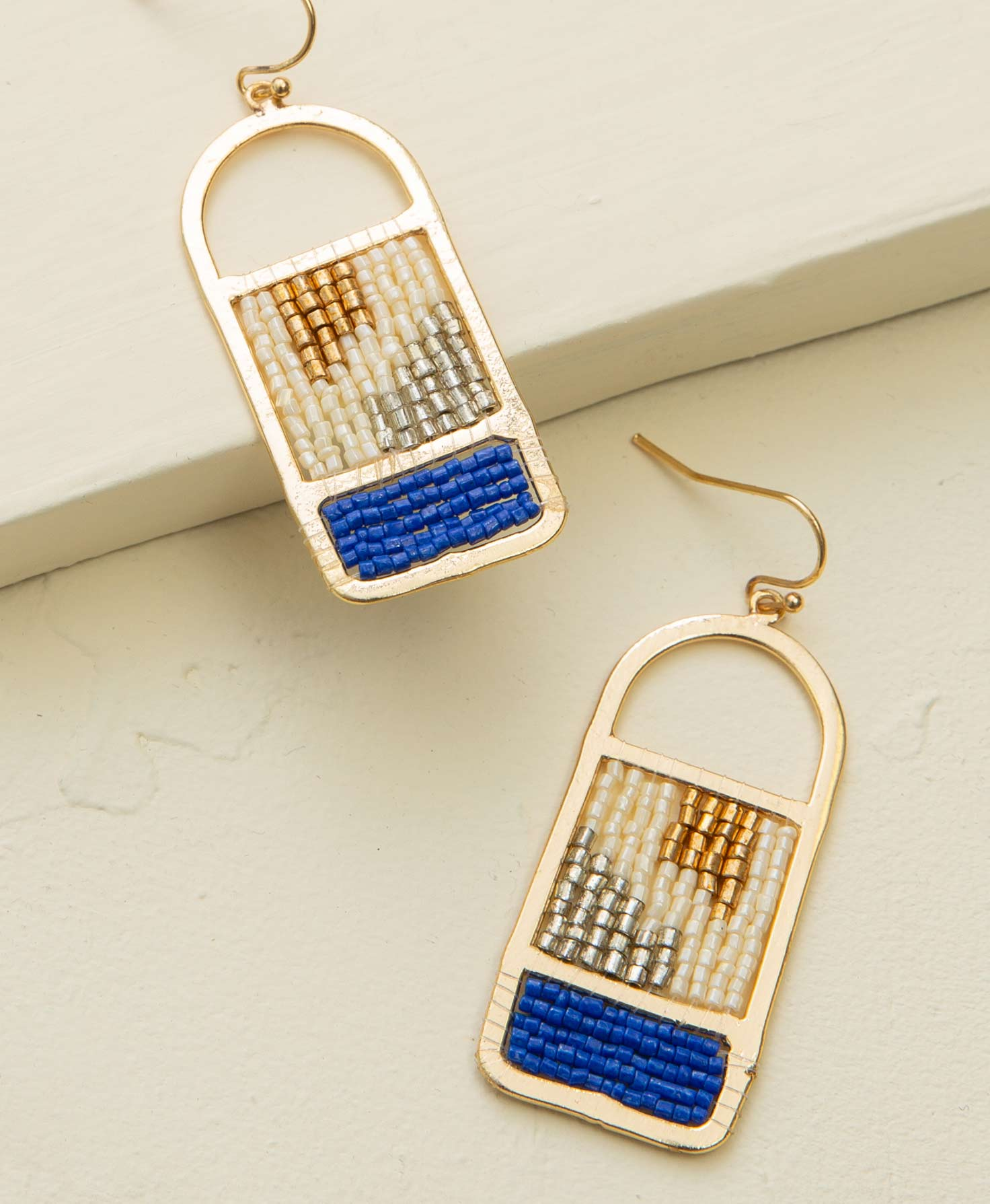 The Peak Earrings lay on a cream-colored platform. A flat brass outline forms a window-like shape. Silver, gold, and cream glass beads are strung across the inside of the window to form a geometric pattern. Bright blue glass beads are strung across the bottom part of the window, forming a solid block of blue.