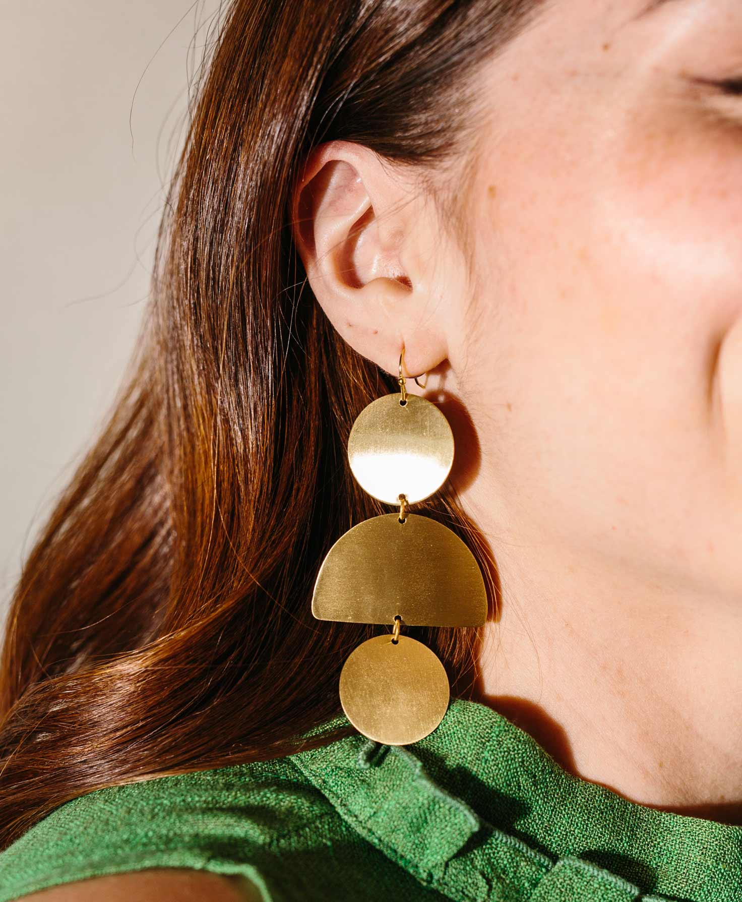 Half of a model's face is shown. She wears a deep green top and the Plaza Earrings. The Earrings make a bold statement as they hang down almost to the model's shoulder. The brass in the earrings shines in the light.