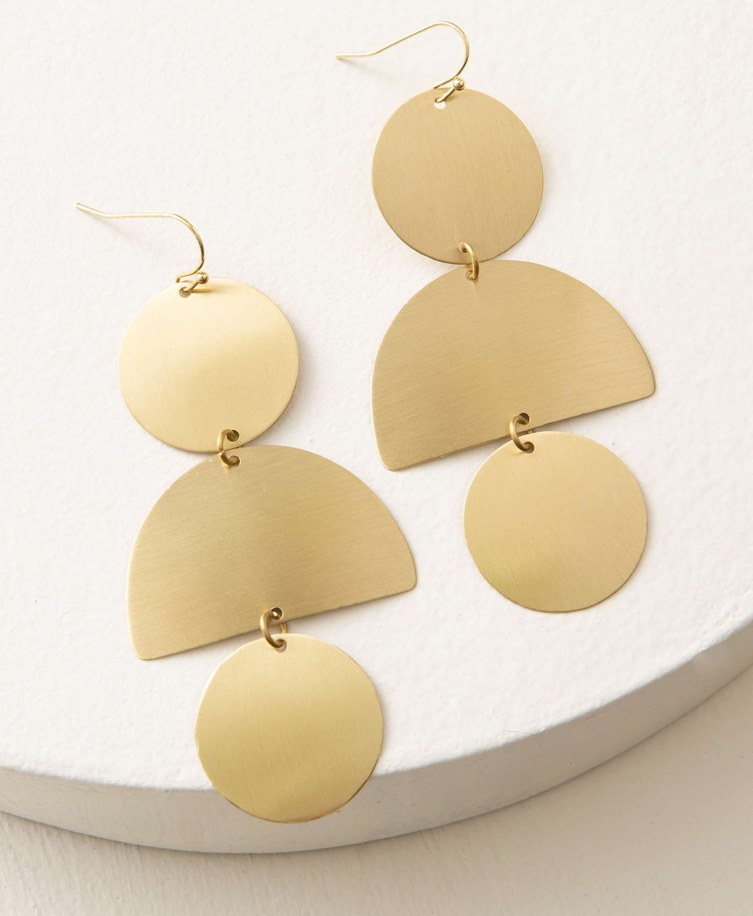 The Plaza Earrings lay on a white surface. They feature flat geometric shapes cut from brass that hang down from a gold ear hook. They have a modern, semi-matte finish that shines, but is not overly glossy. At the top of the earring is a brass circle shape. Connected to this is a brass semi-circle with its flat side facing down. Connected to this shape is a brass circle identical to the first. These statement earrings hang down 3