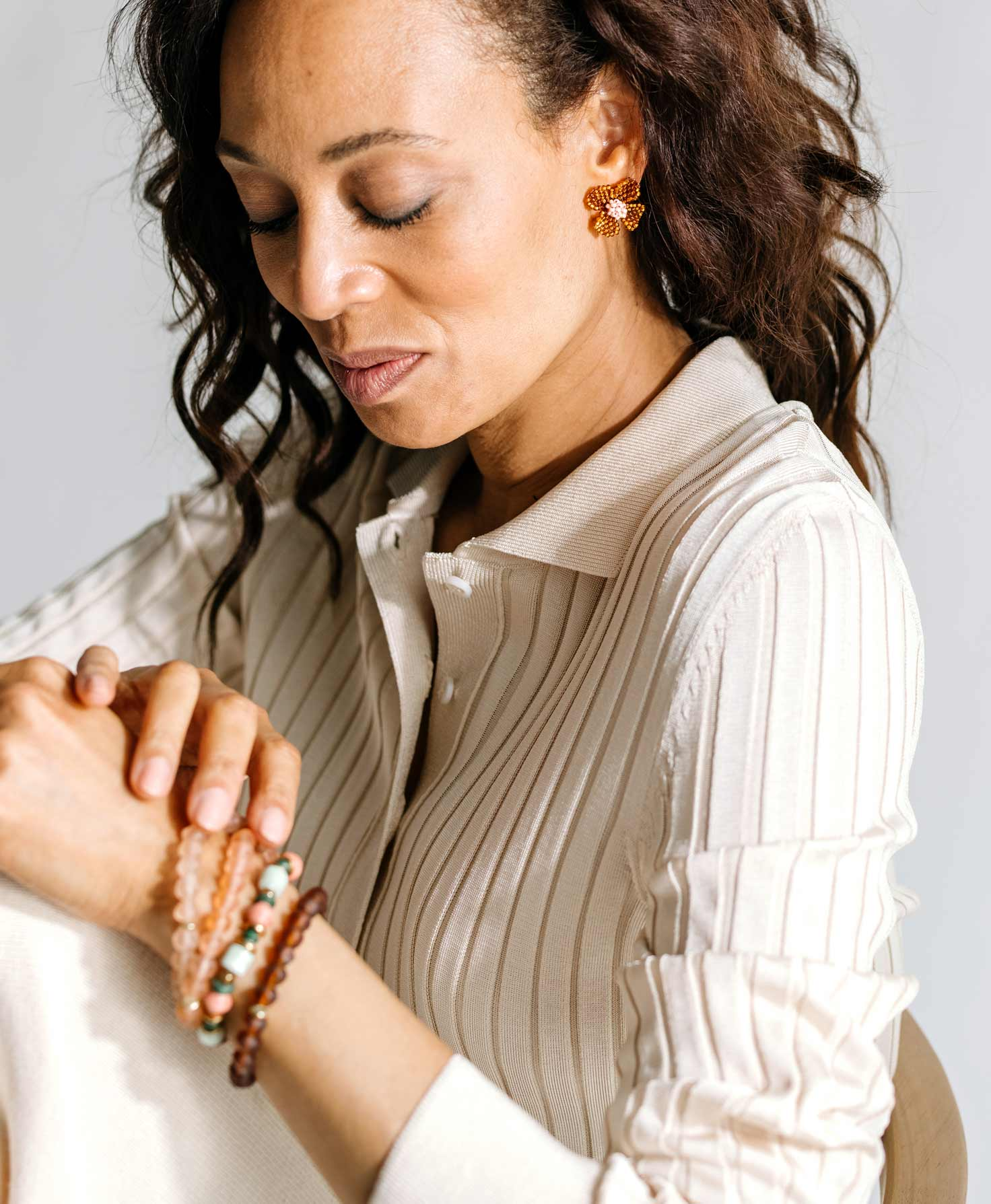 A model wears the Posy Bracelet layered with three glass bracelets from the Bracelet Bar in complementary shades of brown and pink. She also wears the Trellis Earrings, which feature a similar color palette.